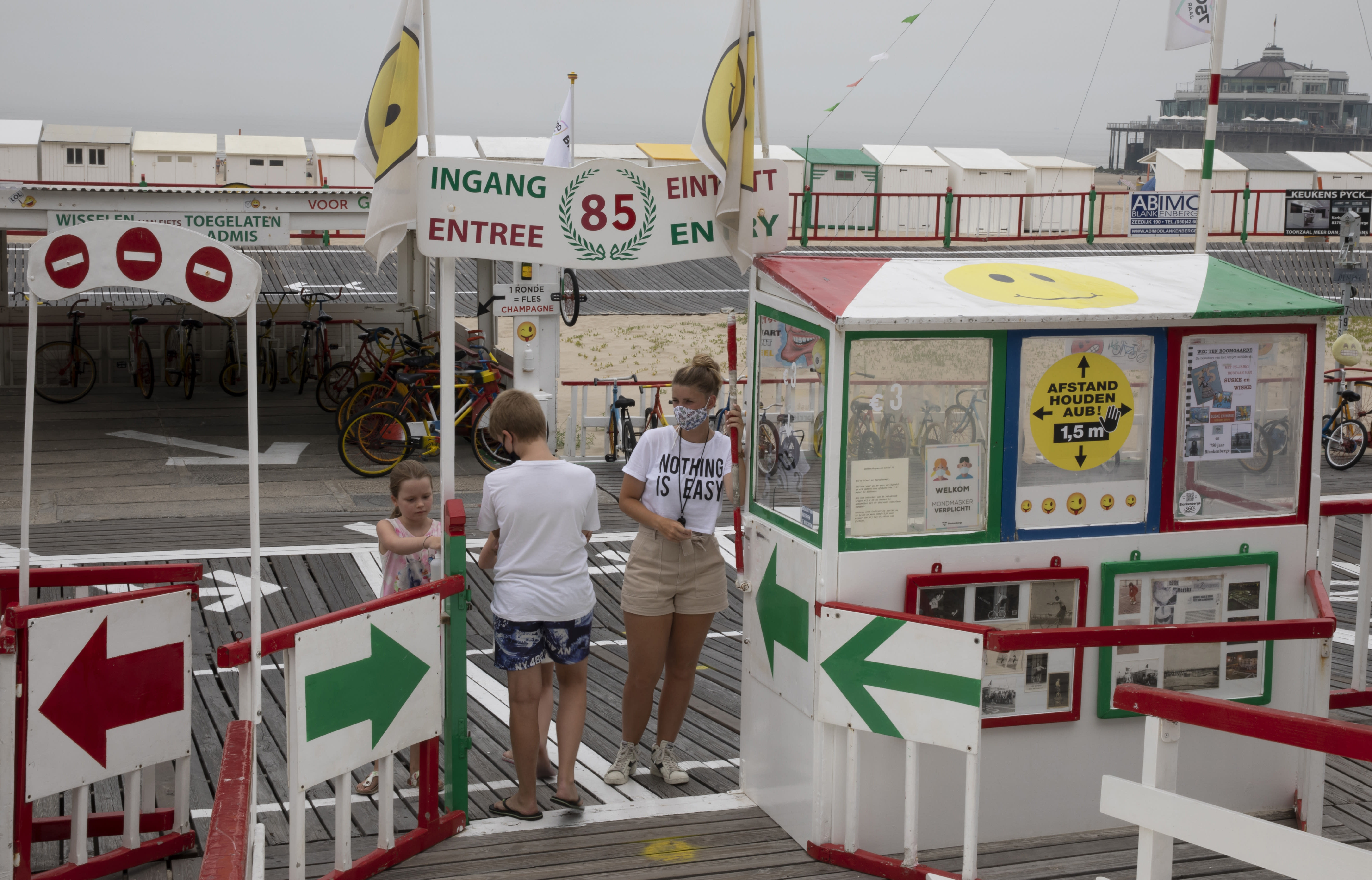 A vendor, asks children to use hand sanitizer before using an amusement ride on the beach at the Belgian seaside resort of Blankenberge, Belgium, Tuesday, Aug. 11, 2020. A skirmish took place on the beach on Saturday, Aug. 8, 2020 which resulted in two coastal communities banning day trippers from the city. (AP Photo/Virginia Mayo)