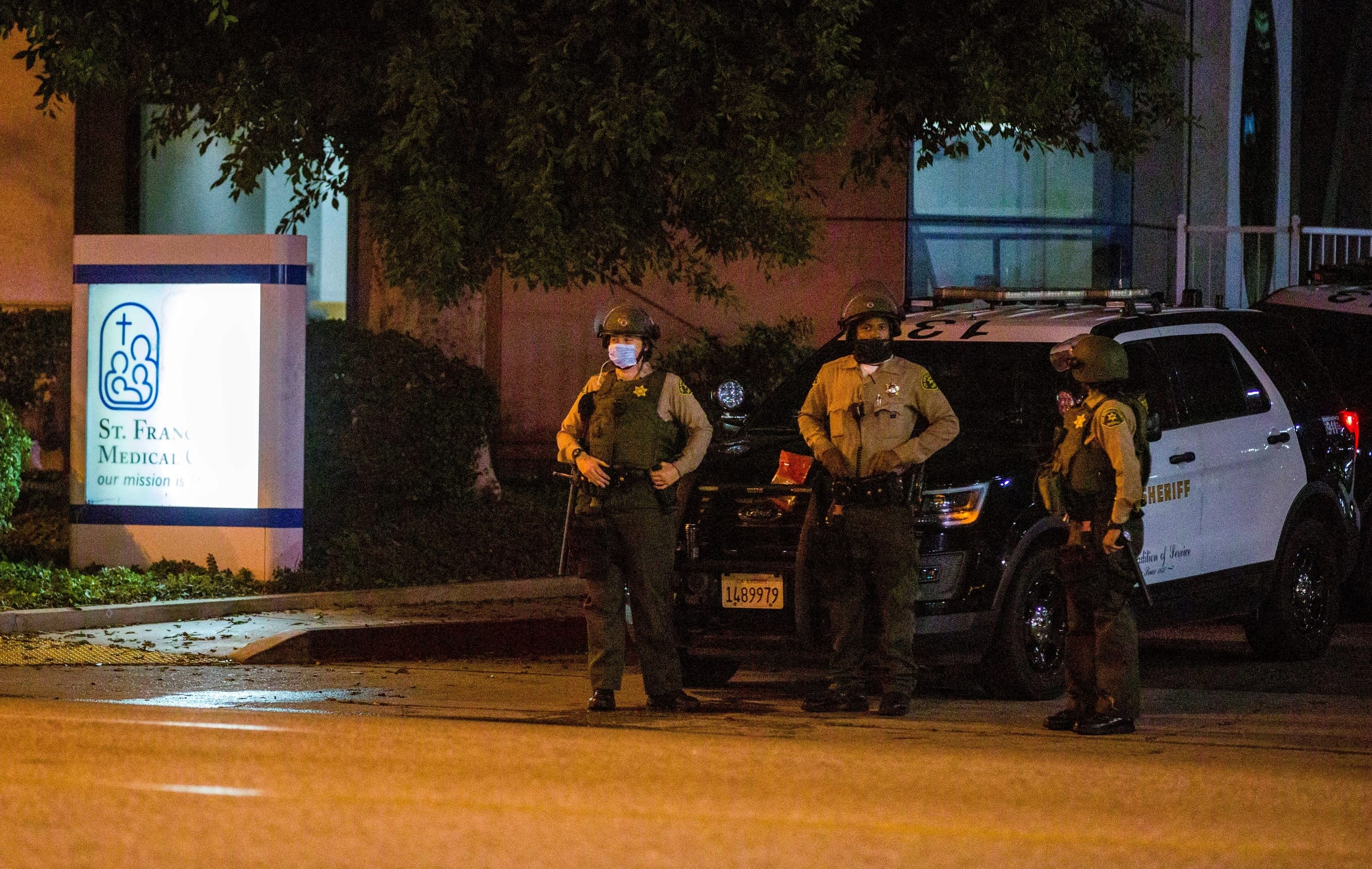 Los Angeles County Sheriff's deputies guard the entrance to St. Francis Medical Center early Monday, Sept. 13, 2020, after two deputies were shot late Saturday, Sept. 12 while sitting inside their patrol vehicle guarding a Metro station in Compton, Calif. (AP Photo/Jintak Han)