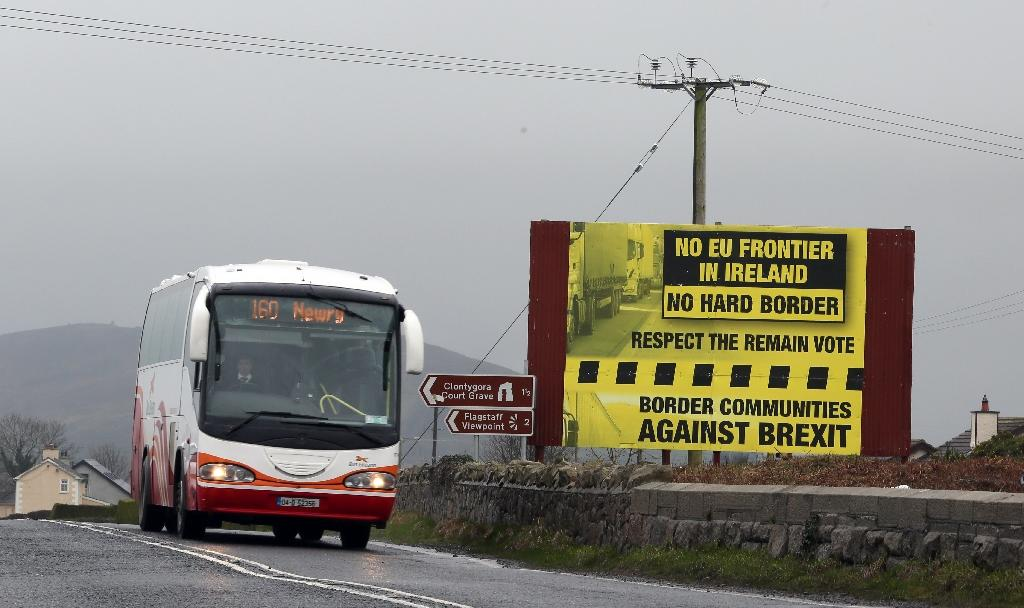 A bus crosses the boder into Northern Ireland from the Irish Republic next to a poster protesting against Brexit near Jonesborough on January 30, 2017 (AFP Photo/Paul FAITH)