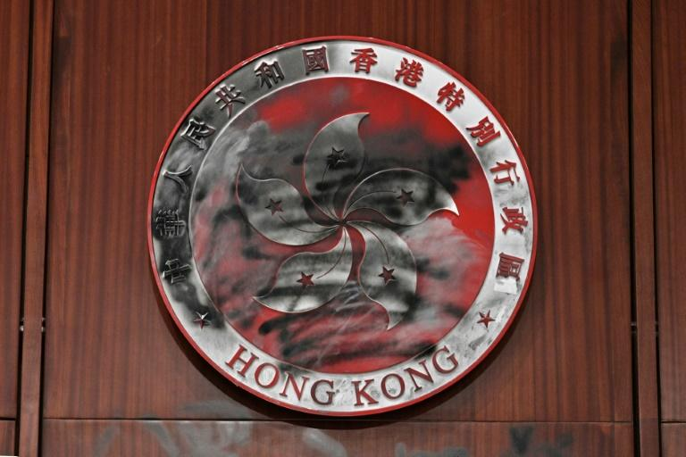 Graffiti is seen on the bauhinia flower emblem of Hong Kong behind the speaker's chair in the main chamber of the Legislative Council during a media tour on July 3, 2019, two days after protesters broke into the complex