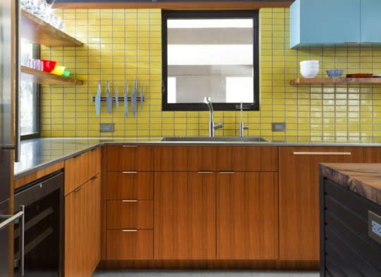 """<p>Interior designers of the 1960s often used streamlined wood cabinetry to add texture and warmth to modern rooms. This trick works wonderfully in contemporary kitchens as well—especially when combining lighter woods with <a href=""""http://www.bobvila.com/slideshow/10-extras-to-diy-for-your-kitchen-48709?bv=yahoo"""" rel=""""nofollow noopener"""" target=""""_blank"""" data-ylk=""""slk:bright accents"""" class=""""link rapid-noclick-resp"""">bright accents</a> and plenty of natural light.</p><p><b>Related: <a href=""""http://www.bobvila.com/slideshow/9-simple-diy-ways-to-reinvent-your-kitchen-cabinets-49215?bv=yahoo"""" rel=""""nofollow noopener"""" target=""""_blank"""" data-ylk=""""slk:9 Simple DIY Ways to Reinvent Your Kitchen Cabinets"""" class=""""link rapid-noclick-resp"""">9 Simple DIY Ways to Reinvent Your Kitchen Cabinets</a> </b> </p><p>Source: Bob Vila</p>"""