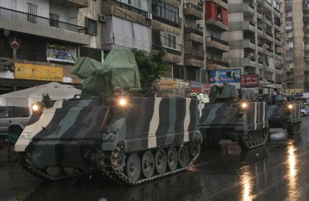 Lebanese army soldiers are seen on their military vehicles as they are deployed on the streets of Tripoli, northern Lebanon, December 3, 2013. REUTERS/Stringer