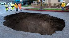 Car hangs on pavement edge before falling into California sinkhole