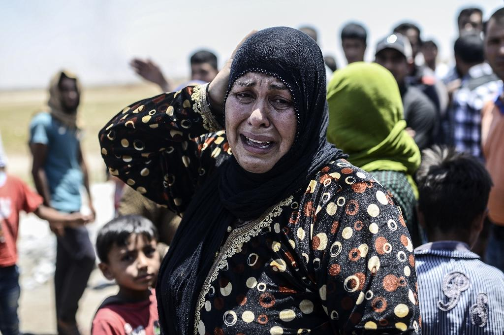 A Syrian woman cries after crossing into Turkey at the Akcakale border crossing on June 14, 2015