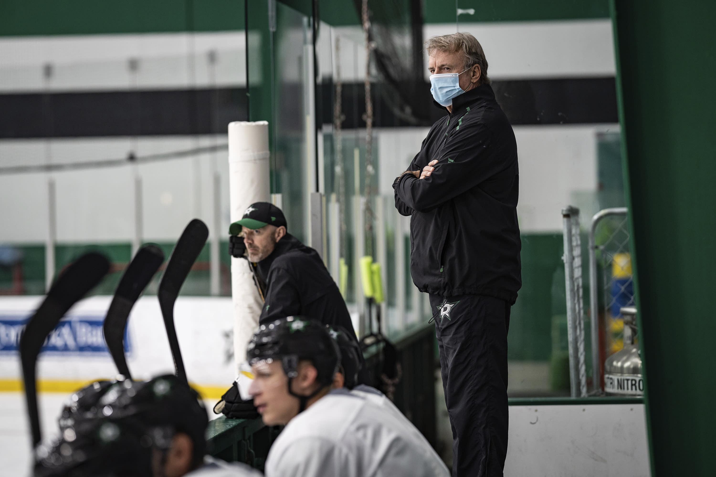 In this photo provided by the Dallas Stars NHL hockey team, interim head coach Rick Bowness watches practice at Comerica Center in Frisco, Texas, Tuesday, July 14, 2020. Bowness, 65, coached from behind the bench the first couple of days of Dallas Stars training camp before lacing up his skates and getting on the ice. Montreal's 60-year-old Claude Julien, Edmonton's 58-year-old Dave Tippett and others are confident in the NHL's protocols as older, more at-risk people during the COVID-19 pandemic. Only one coach, Florida's 63-year-old assistant Mike Kitchen, has opted out of hockey's return. (Jeff Toates/Dallas Stars via AP)