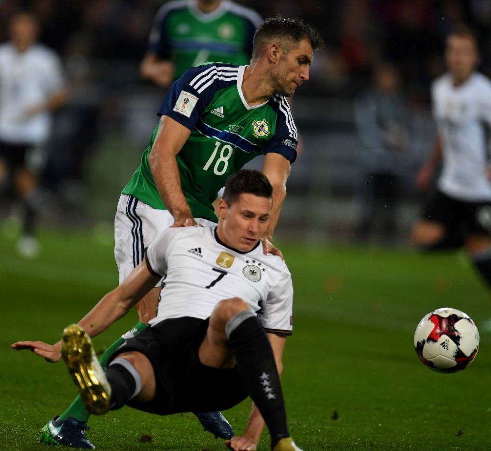 Germany's midfielder Julian Draxler (R) and Northern Ireland´s Aaron Hughes during the WC 2018 football qualification match between Germany and Northern Ireland in Hanover, Germany on October 11, 2016