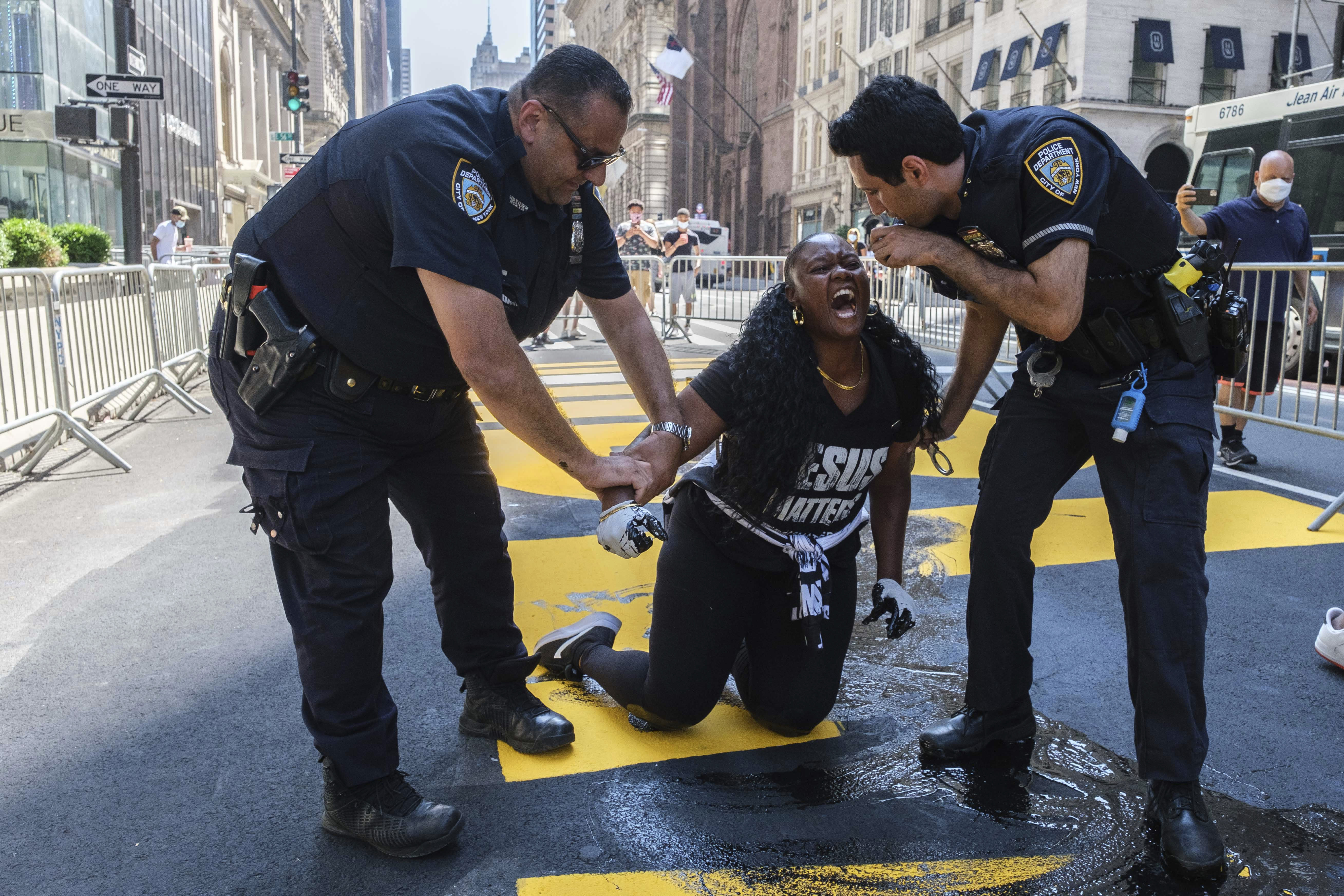 """New York Police Department officers attempt to detain a protester who defaced with black paint the Black Lives Matter mural outside of Trump Tower on Fifth Avenue Saturday, July 18, 2020, in the Manhattan borough of New York. The """"Black Lives Matter"""" street mural in front of Manhattan's Trump Tower has been defaced with paint for the third time in a week. (AP Photo/Yuki Iwamura)"""