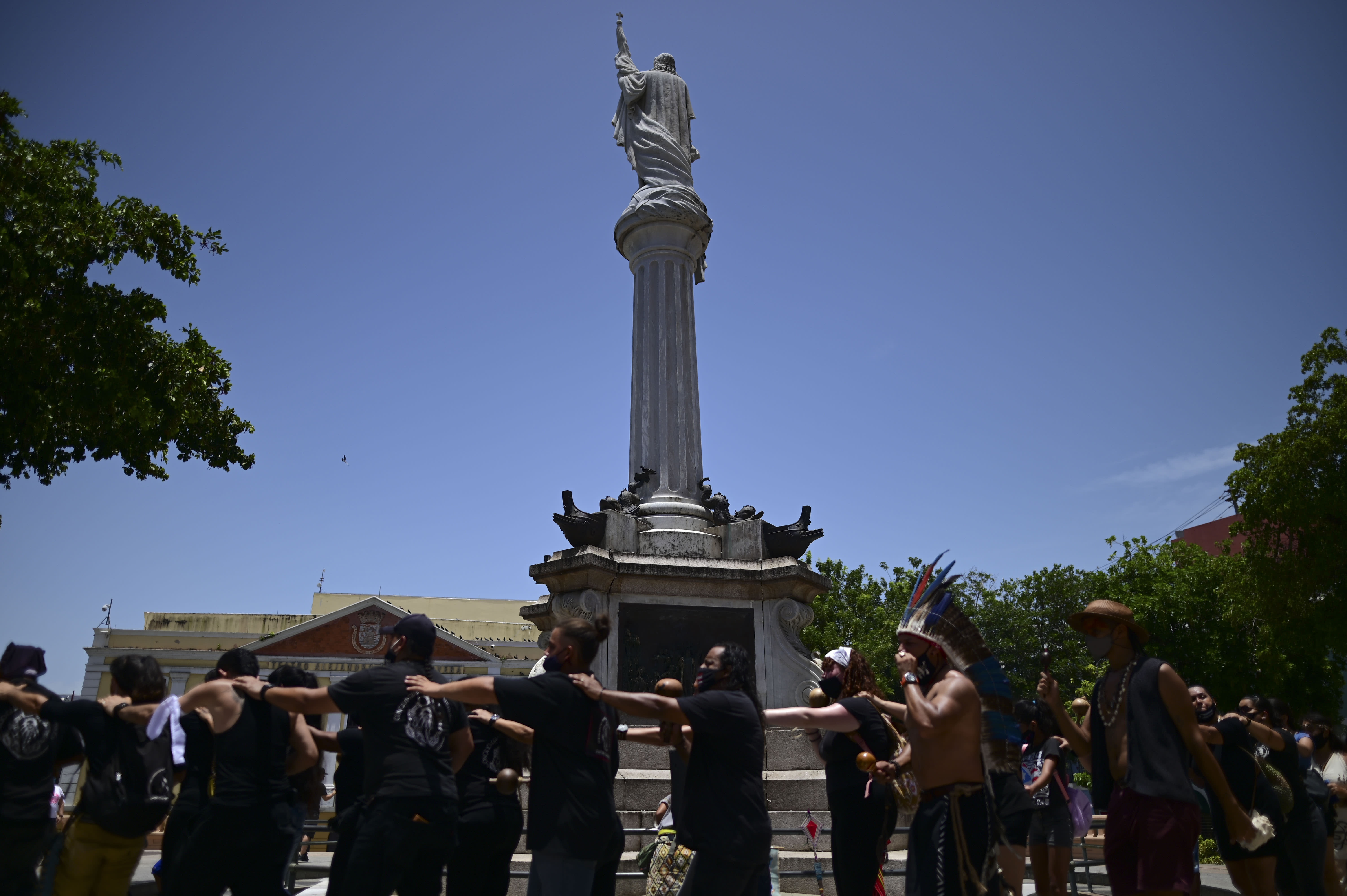A group of activists surround a monument to Christopher Columbus demanding statues and street names commemorating symbols of colonial oppression be removed, in San Juan, Puerto Rico, Saturday, July 11, 2020. Dozens of activists marched through the historic part of Puerto Rico's capital on Saturday to demand that the U.S. territory's government start by removing statues, including those of explorer Christopher Columbus. (AP Photo/Carlos Giusti)