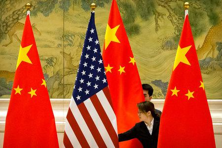 Chinese staffers adjust U.S. and Chinese flags before the opening session of trade negotiations between U.S. and Chinese trade representatives at the Diaoyutai State Guesthouse in Beijing, Thursday, Feb. 14, 2019. Mark Schiefelbein/Pool via REUTERS/Files