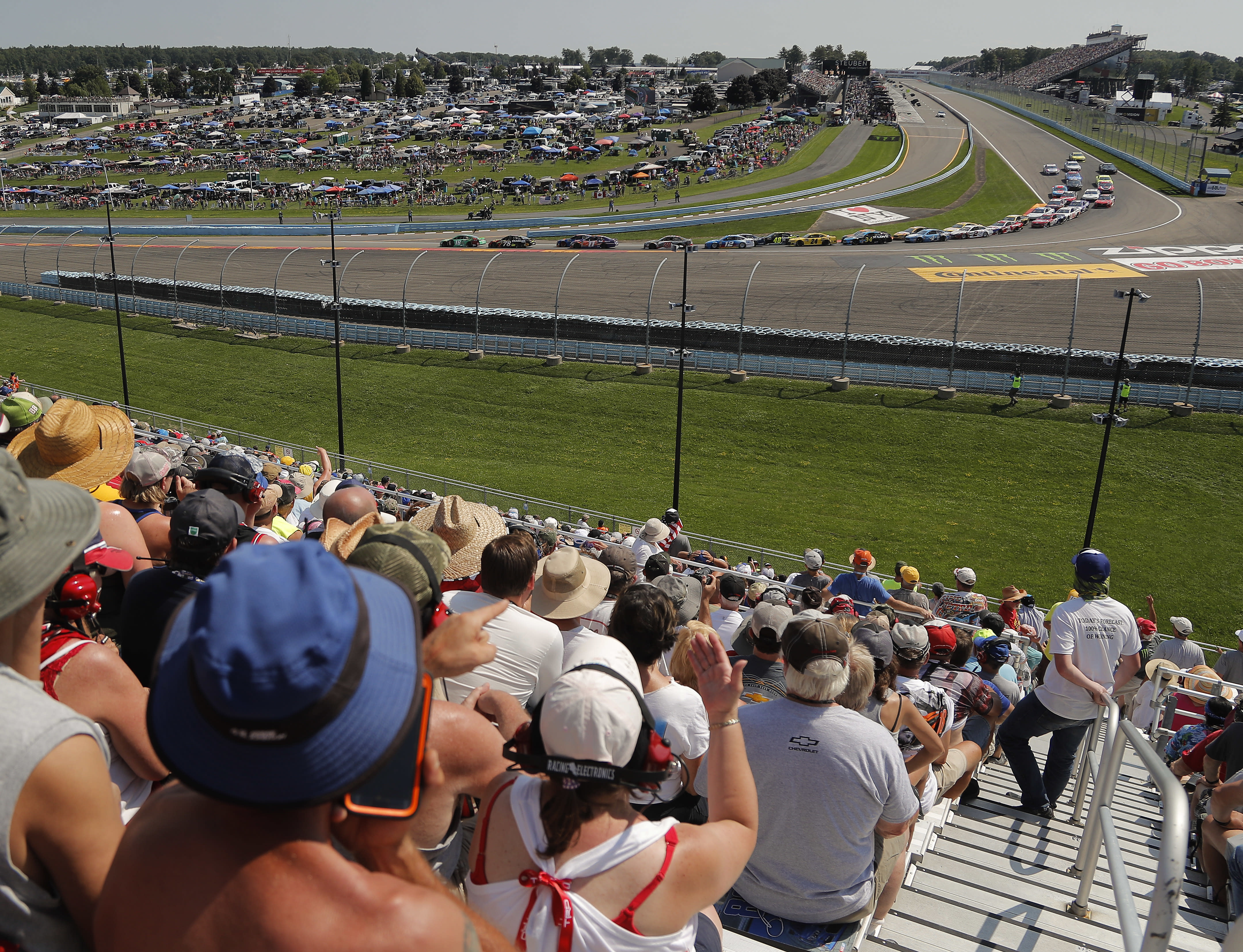 """FILE - In this Aug. 5, 2018, file photo, spectators watch as drivers come around Turn 1 during a restart after a caution during a NASCAR Cup Series auto race in Watkins Glen, N.Y. Three months after its opening day was canceled by the coronavirus pandemic, Watkins Glen International is hosting car clubs again as NASCAR weekend looms in mid-August. """"Everybody is excited about getting back in the saddle. I know we are,"""" track president Michael Printup said. (AP Photo/Julie Jacobson, File)"""