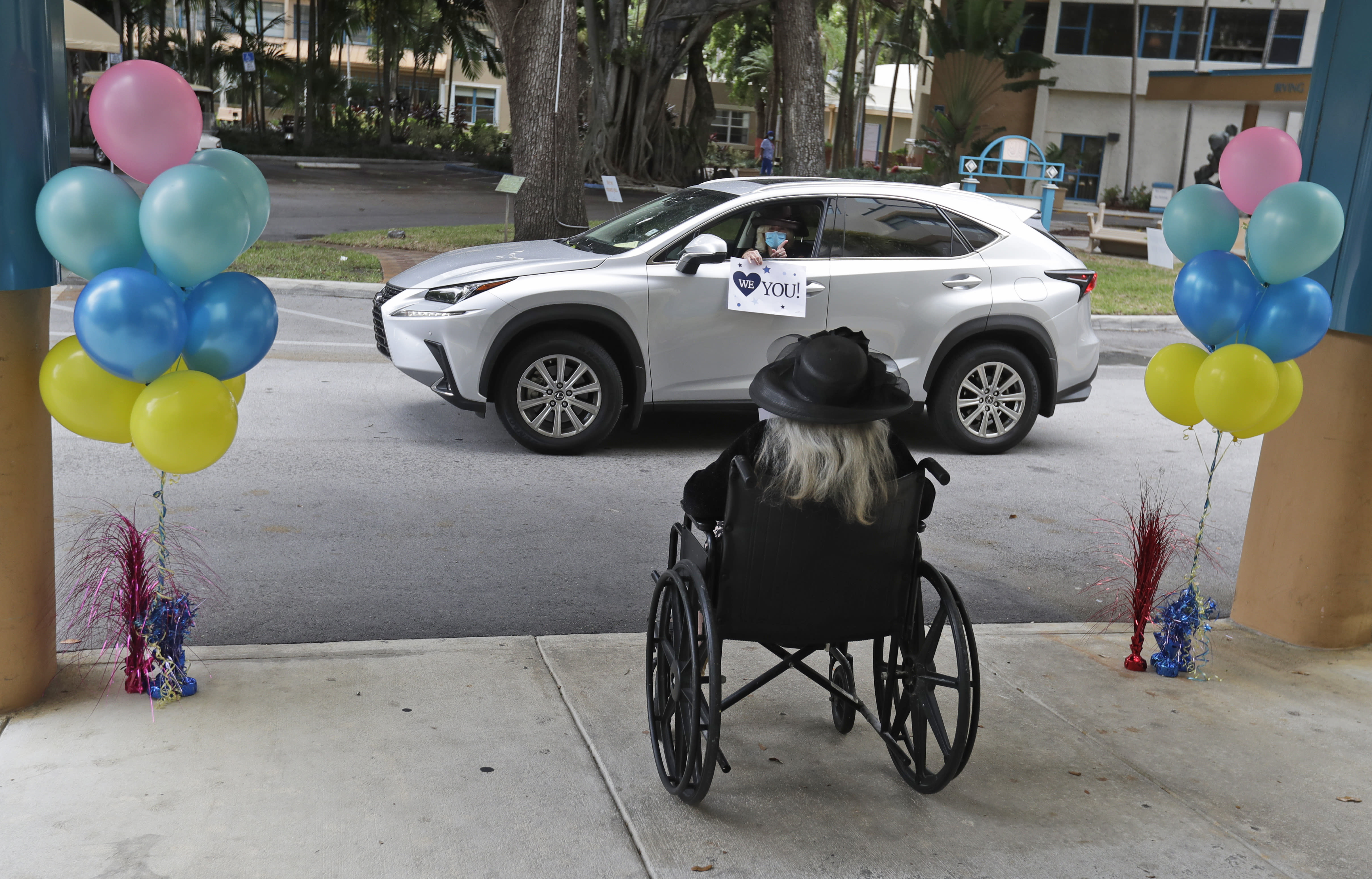 Frances Reaves, in car, pays a visit to her friend Margaret Choinacki, foreground, 87, who has no other family members left because her husband and daughter have died, Friday, July 17, 2020, at Miami Jewish Health in Miami. Miami Jewish Health has connected more than 5,000 video calls and allowed drive-by visits where friends and family emerge through sunroofs to see their loved ones. (AP Photo/Wilfredo Lee)