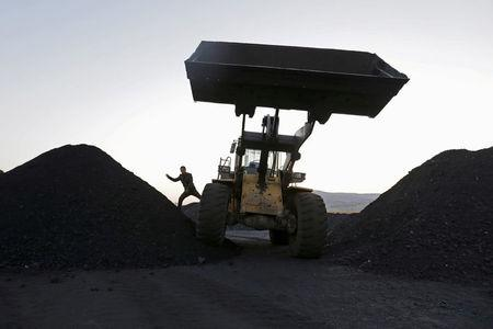 FILE PHOTO: A driver gets off a loading vehicle at a small coal depot near a coal mine on the outskirts of Jixi, in Heilongjiang province, China, October 23, 2015. REUTERS/Jason Lee/File Photo