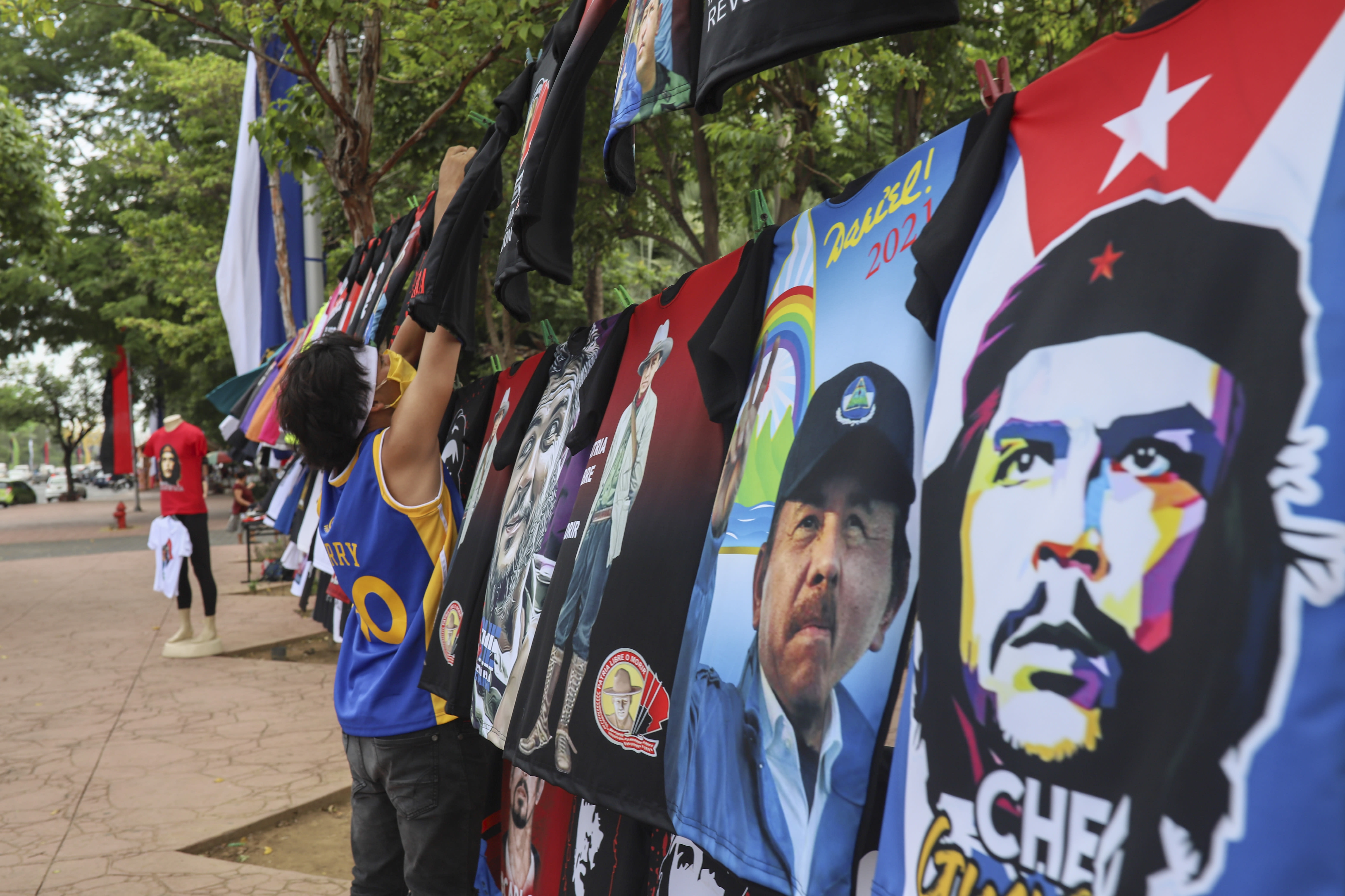 """A vendor sells T-shirts promoting Nicaraguan President Daniel Ortega and The Sandinista National Liberation Front ruling party on the sidelines of a new monument, called the Peace Bell, before its inauguration ceremony later in the day in Managua, Nicaragua, Friday, July 17, 2020. Nicaraguan President Daniel Ortega's government is being deterred by the new coronavirus from holding the usual mass celebration to mark the victory of the country's revolution July 19, and will instead unveil a new addition to its collection of monuments. At right is a T-shirt of Cuba's revolutionary hero Ernesto """"Che"""" Guevara. (AP Photo/Alfredo Zuniga)"""
