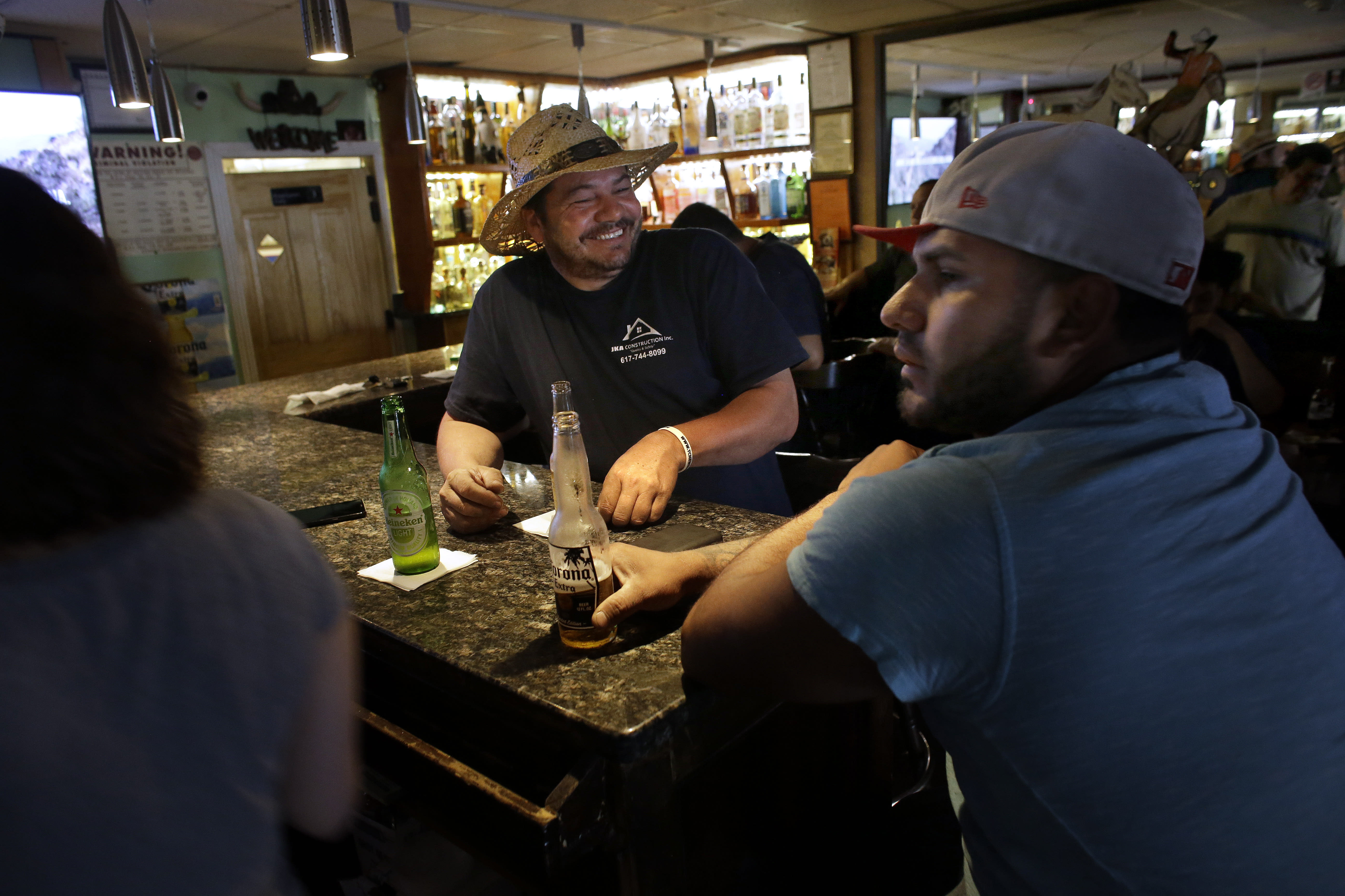 In this Thursday, June 27, 2019 photo patrons, who asked that they not be identified by name, are seated in a bar, in Chelsea, Mass. In the last two decades Chelsea and its neighbors Everett, Malden, Revere and Lynn have all become the region's most diverse communities, a Boston Indicators study found. (AP Photo/Steven Senne)