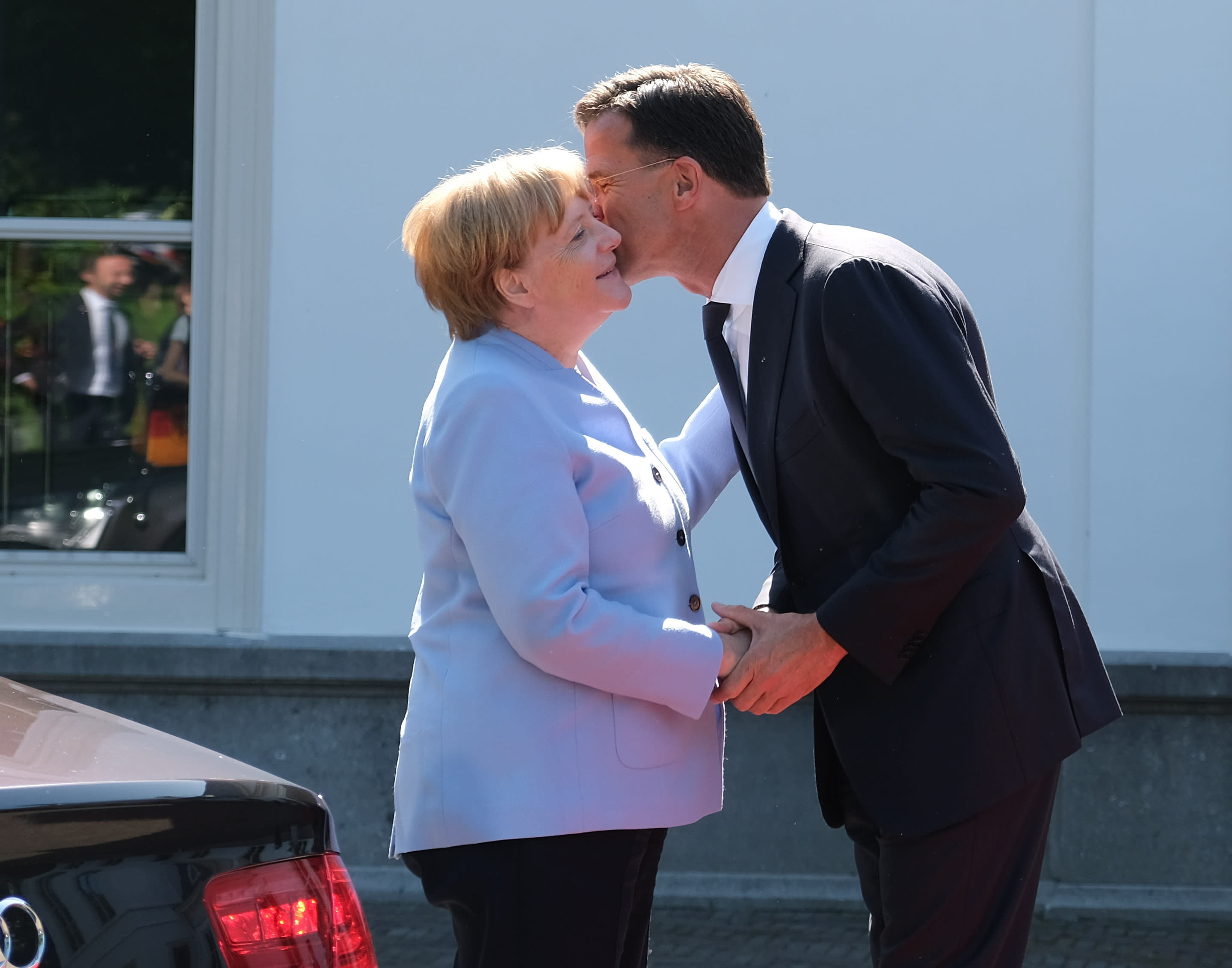 Dutch Prime Minister Mark Rutte, right, greets German Chancellor Angela Merkel in The Hague, Netherlands, Thursday Aug. 22, 2019. Merkel and key Cabinet ministers are meeting their Dutch counterparts Thursday to discuss ways of tackling climate change together, as Germany is set to miss its emissions goals for 2020 by a wide margin.(AP Photo/Mike Corder)