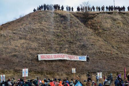 FILE PHOTO -- Protesters raise a banner on Turtle Island on Thanksgiving day during a protest against plans to pass the Dakota Access pipeline near the Standing Rock Indian Reservation, near Cannon Ball, North Dakota, U.S. November 24, 2016. REUTERS/Stephanie Keith/File Photo