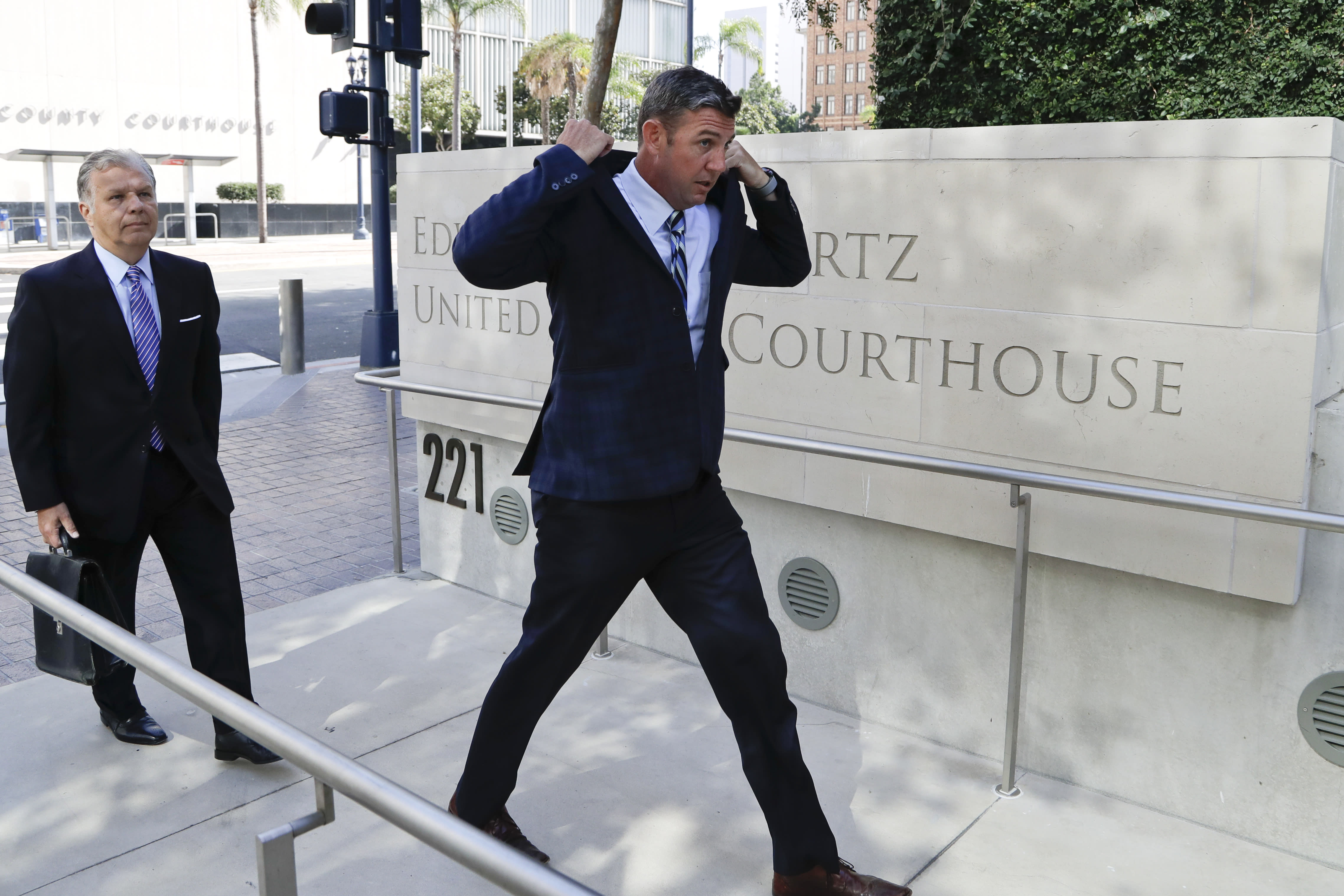 U.S. Rep. Duncan Hunter, right, arrives for an arraignment hearing Thursday, Aug. 23, 2018, in San Diego. Hunter and his wife were indicted Tuesday on federal charges that they used more than $250,000 in campaign funds for personal expenses that ranged from groceries to golf trips and lied about it in federal filings, prosecutors said. (AP Photo/Gregory Bull)