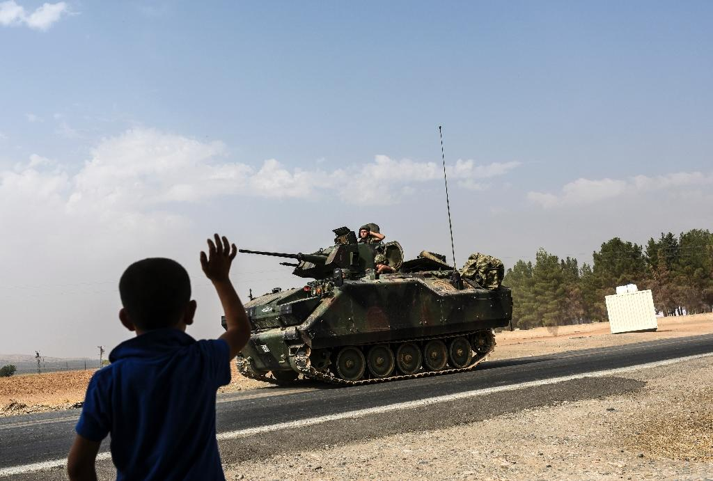 A Turkish boy waves to Turkish tank convoy driving into Syria from the border city of Karkamis in the southern region of Gaziantep, on August 26, 2016 (AFP Photo/Bulent Kilic)