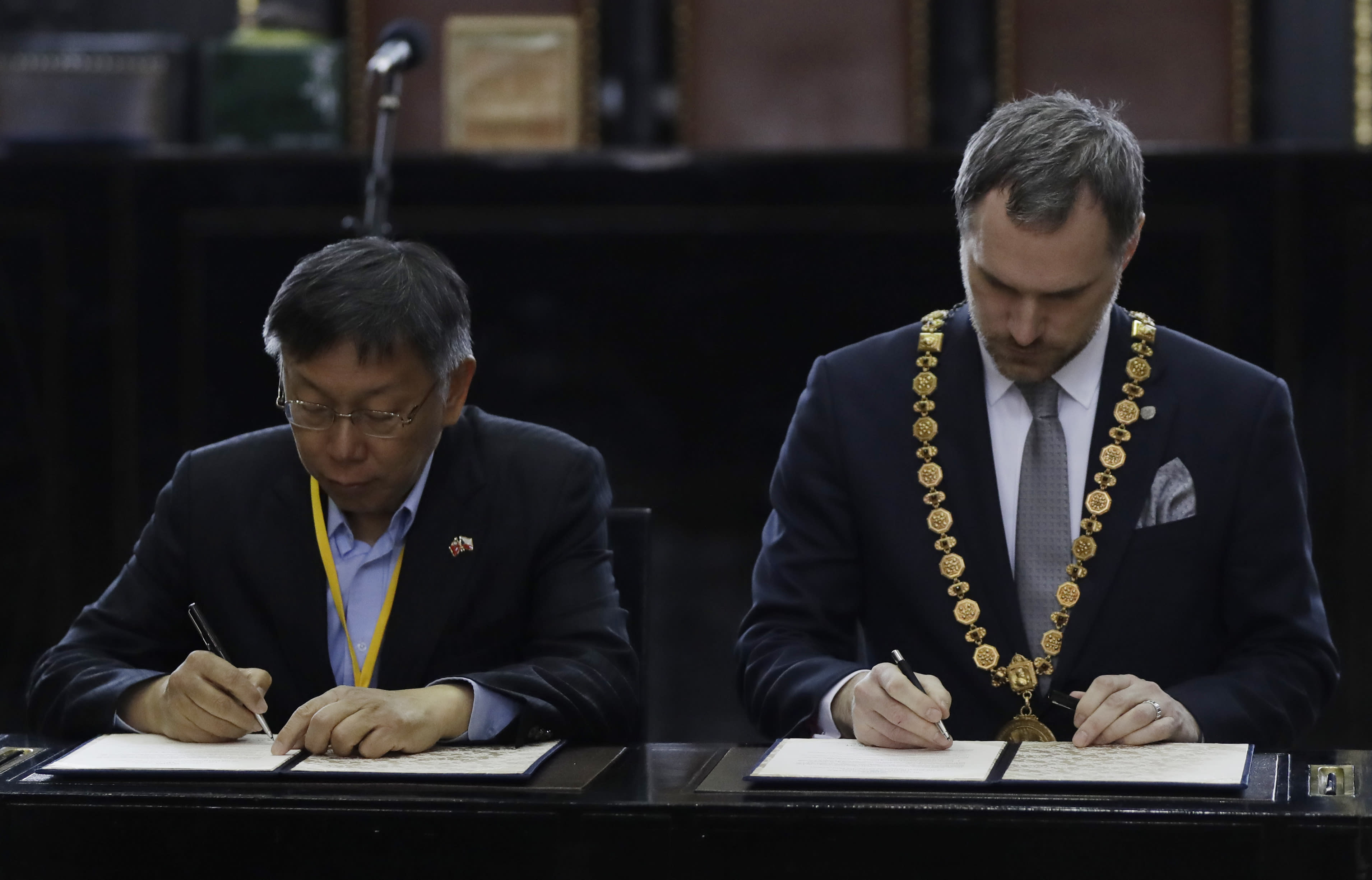 Mayor of Prague Zdenek Hrib, right, and Taipei city mayor Ko Wen-je sign a partnership agreement between the two cities at at the Old Town City Hall in Prague, Czech Republic, Monday, Jan. 13, 2020. The signing comes three months after Prague revoked a similar sister-city agreement with Beijing, an action that angered China. (AP Photo/Petr David Josek)