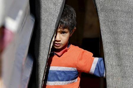 A Syrian refugee boy stands in front of his family's tent in Al Zaatari refugee camp, in the Jordanian city of Mafraq