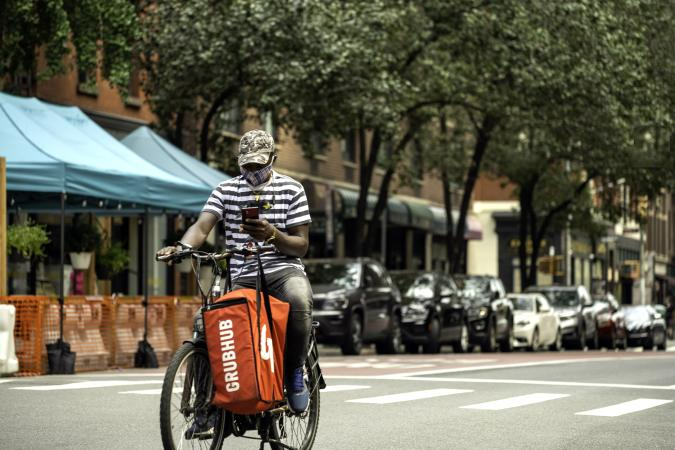 New York, NY, USA - August 23, 2020: A Grubhub food delivery man rides south down Lexington Avenue on Manhattan's upper east side in the east 90's on a quiet Sunday in August. Masks remain mandatory in NYC due to the coronavirus.