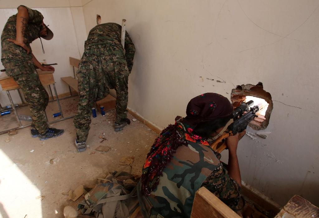 Fighters from the Kurdish People's Protection Units (YPG) take position in a classroom in the village of Maaruf near Hasakeh on July 16, 2015 (AFP Photo/Youssef Karwashan)
