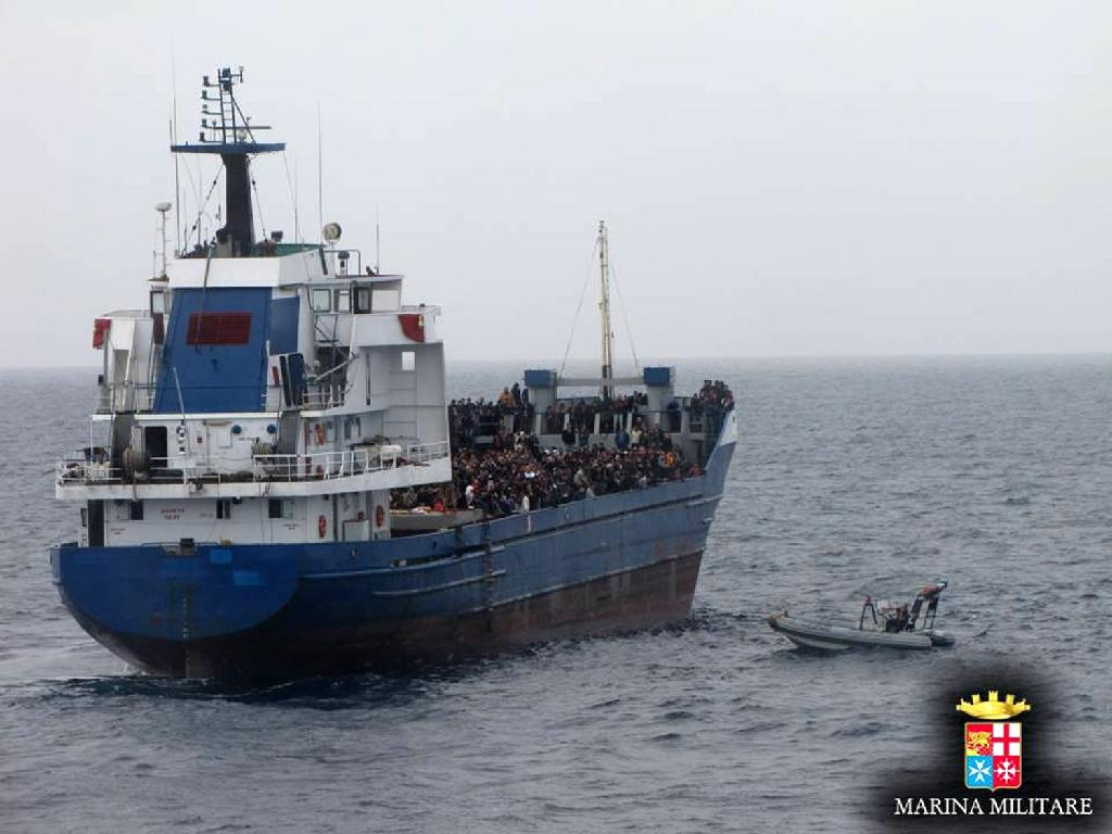 """Handout picture released by the Italian Navy on November 20, 2014, shows migrants sitting in the merchant boat """"St Jonhe's"""" which is towed by a military ship during the rescue operation off the coast of Sicily (AFP Photo/)"""