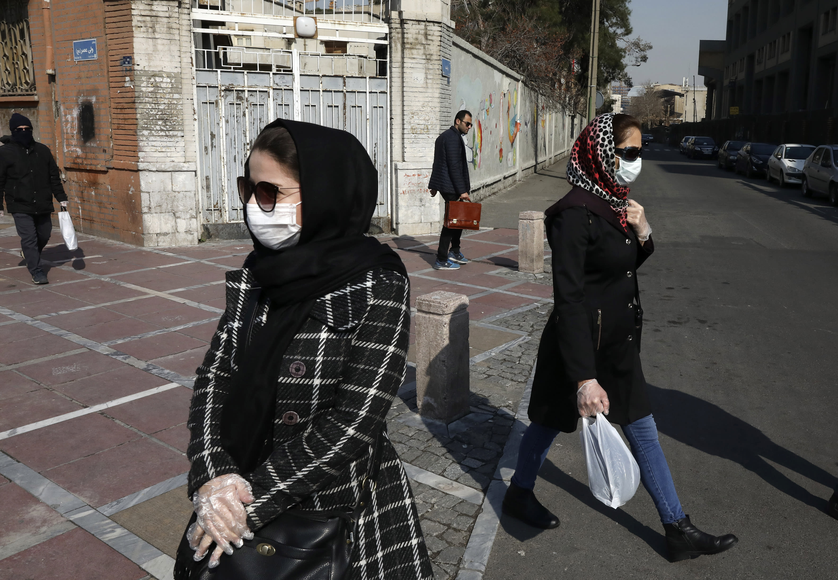 Pedestrians walk as some of them wear masks in downtown Tehran, Iran, Thursday, Feb. 27, 2020. Amid fear and uncertainty caused by the spread of a new virus, Iranians are taking extra caution to avoid getting infected, as authorities canceled Friday prayers in Tehran, Qom and other cities. (AP Photo/Vahid Salemi)