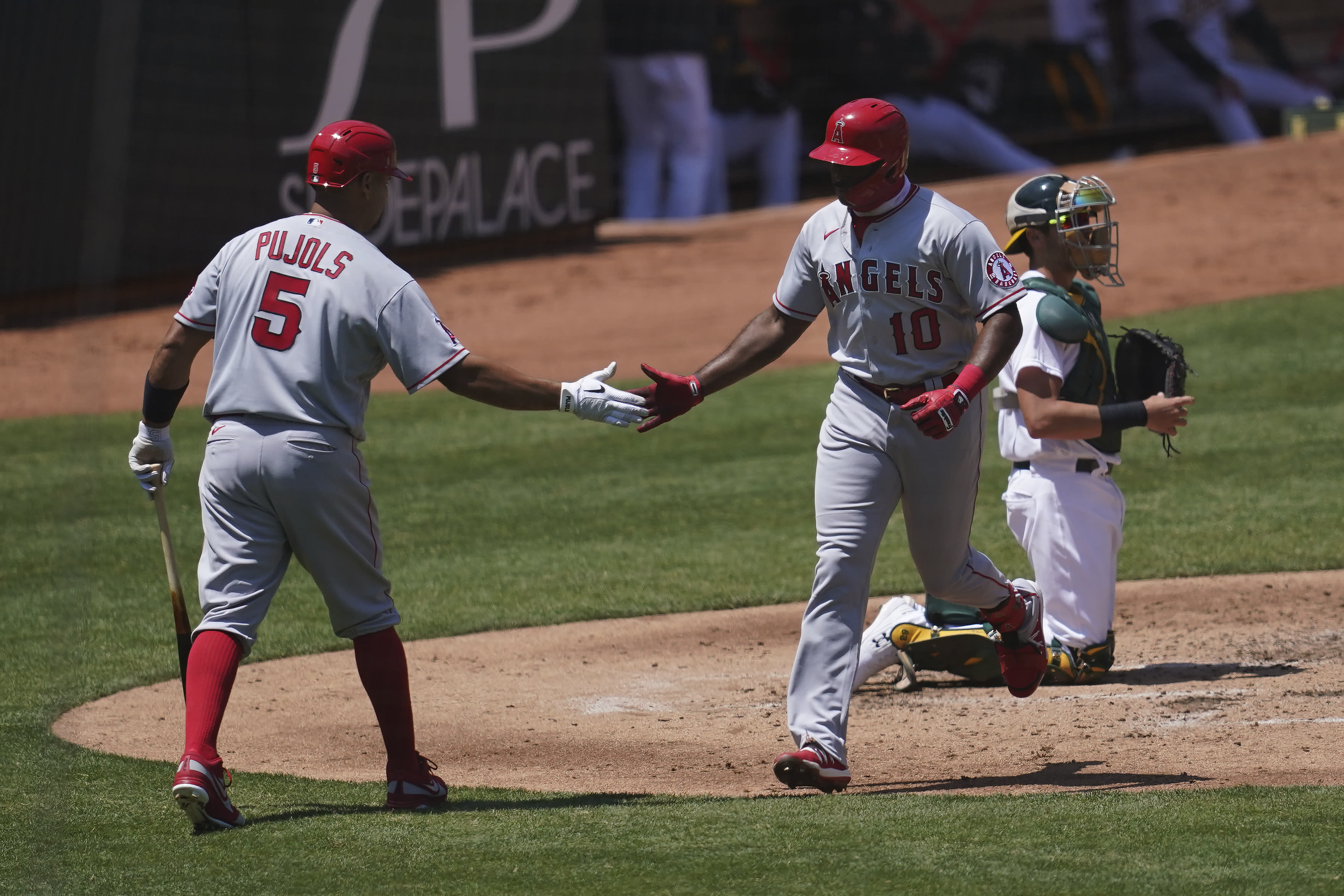 Los Angeles Angels' Justin Upton (10) is congratulated by Albert Pujols after hitting a solo home run against the Oakland Athletics during the fourth inning of a baseball game in Oakland, Calif., Saturday, July 25, 2020. Athletics catcher Austin Allen, right, looks on. (AP Photo/Jeff Chiu)