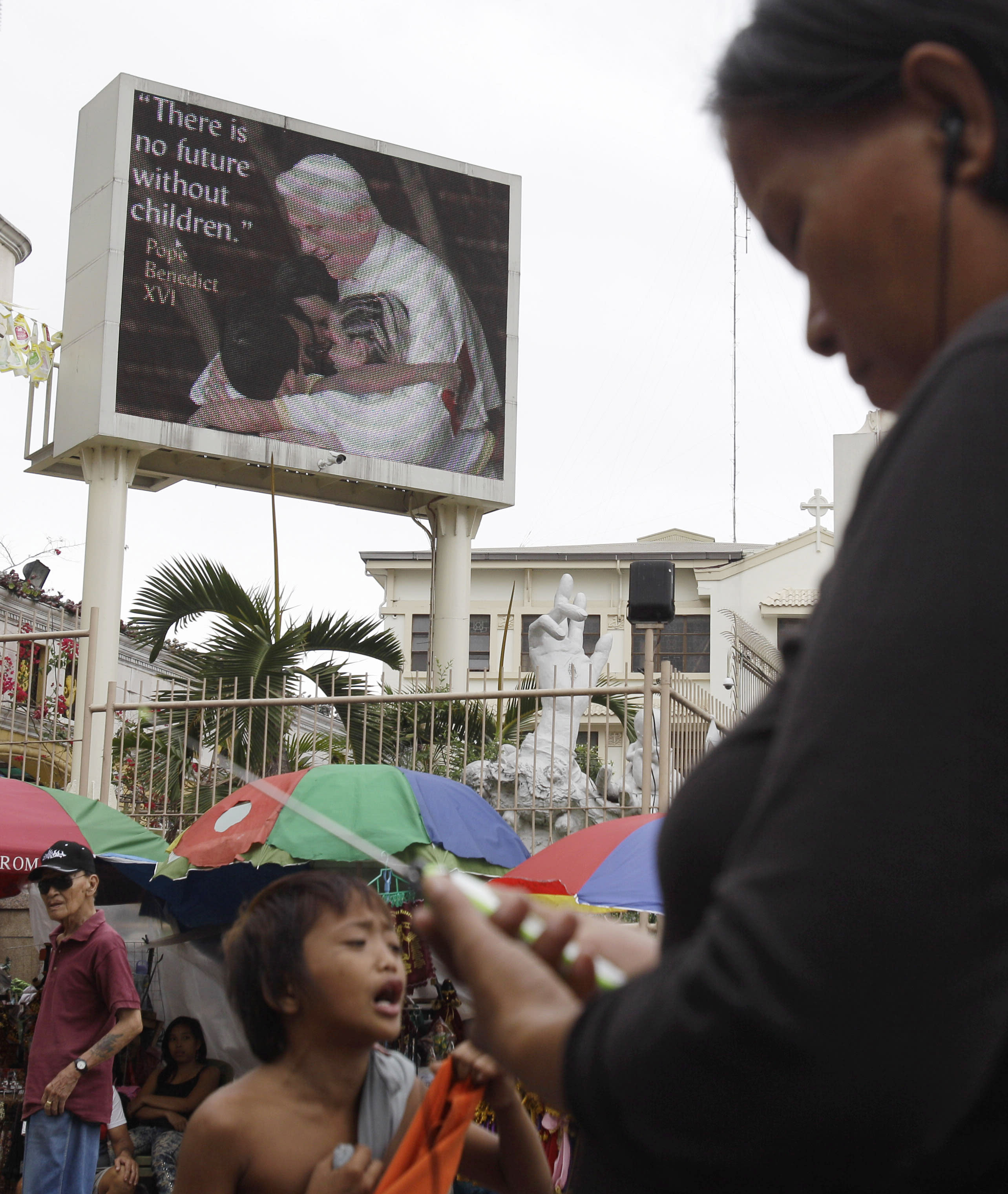 A picture of Pope Benedict XVI is shown on an electric signboard outside the Roman Catholic Minor Basilica of the Black Nazarene in downtown Manila, Philippines on Thursday, Jan. 3, 2013. Philippine President Benigno Aquino III last month signed the Responsible Parenthood and Reproductive Health Act of 2012. The law that provides state funding for contraceptives for the poor pitted the dominant Roman Catholic Church in an epic battle against the popular Aquino and his followers. (AP Photo/Aaron Favila)
