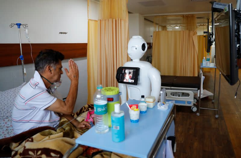A patient suffering from the coronavirus disease (COVID-19) speaks to his family members, using a robot named 'Mitra' at a hospital in Noida