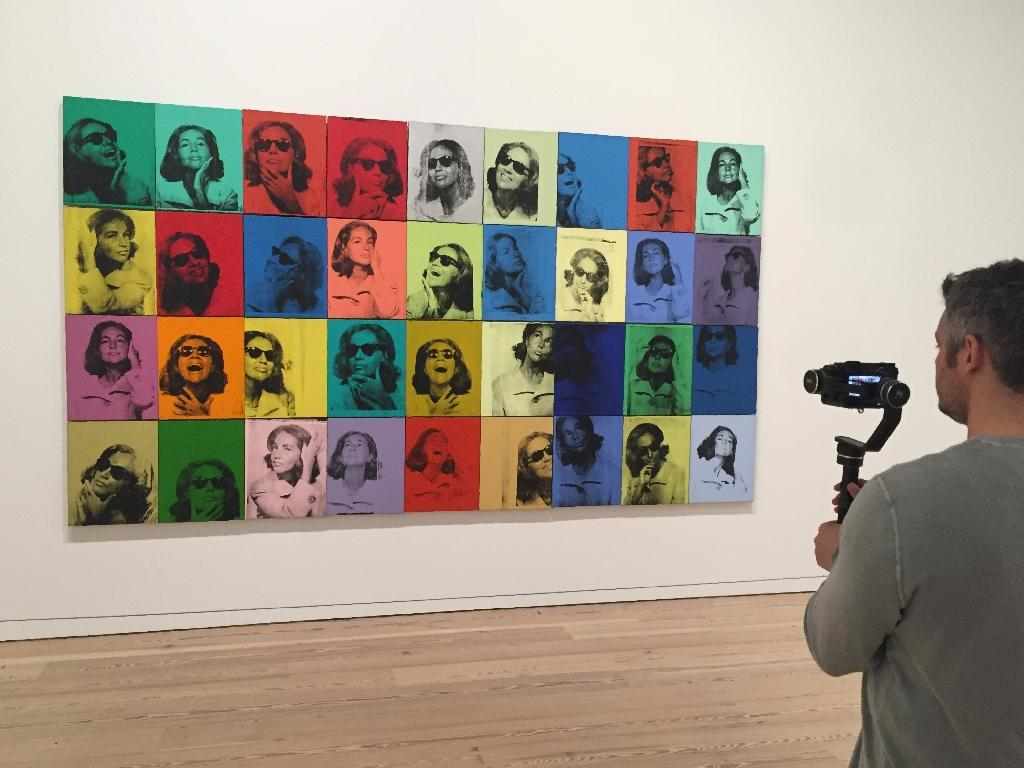 """A man films the painting """"Ethel Scull 36 Times"""" (1963) by Andy Warhol during a press preview of the exhibition """"Andy Warhol -- From A to B and Back Again"""" at the Whitney Museum in New York (AFP Photo/Thomas URBAIN)"""