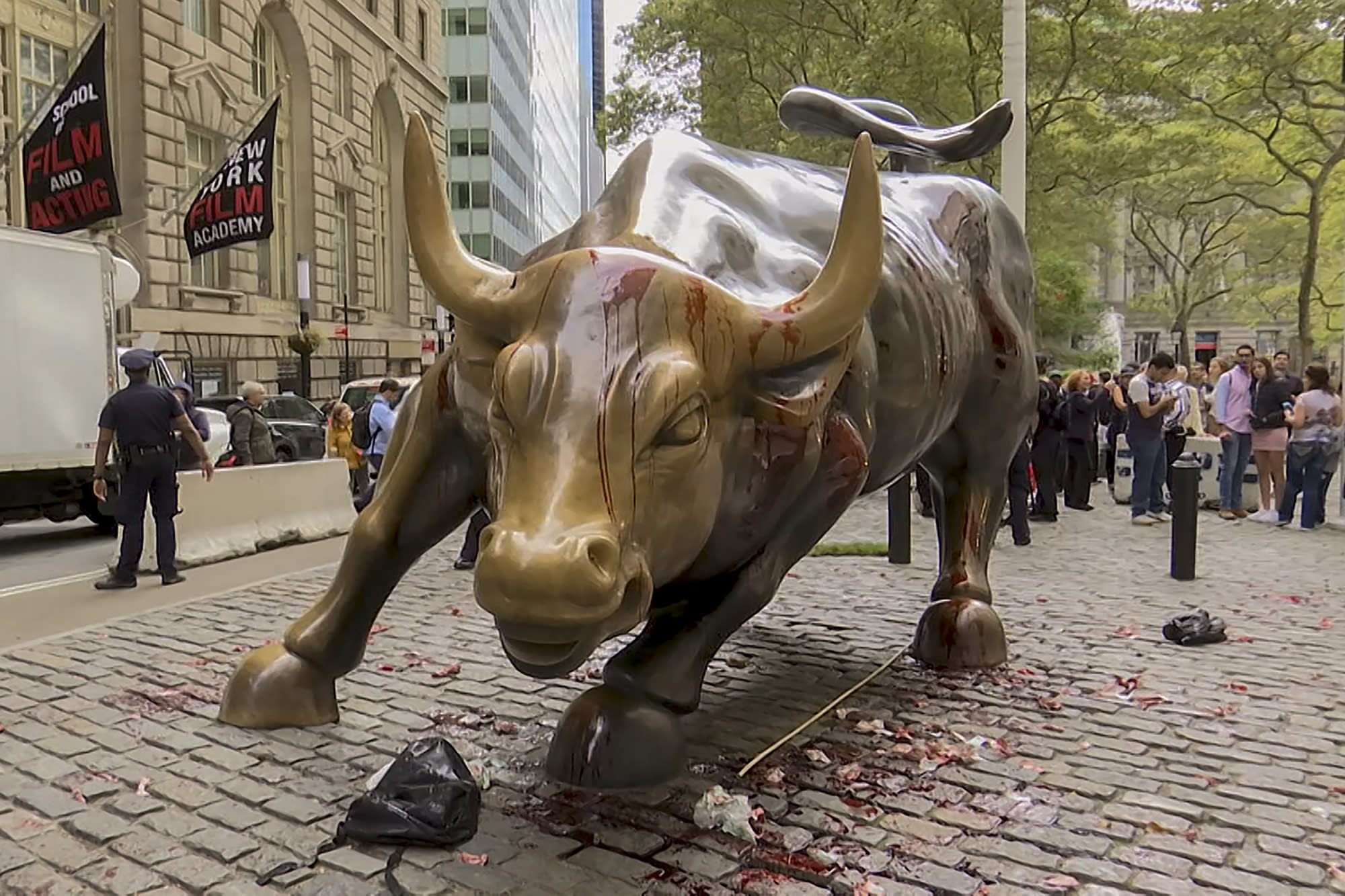 "In this freeze frame made from a video stage blood covers the iconic ""Charging Bull"" statue near Wall Street on Monday Oct. 7, 2019, in New York. Demonstrators say they were protesting against a lack of government action against climate change. (AP Photo/Ted Shaffrey)"