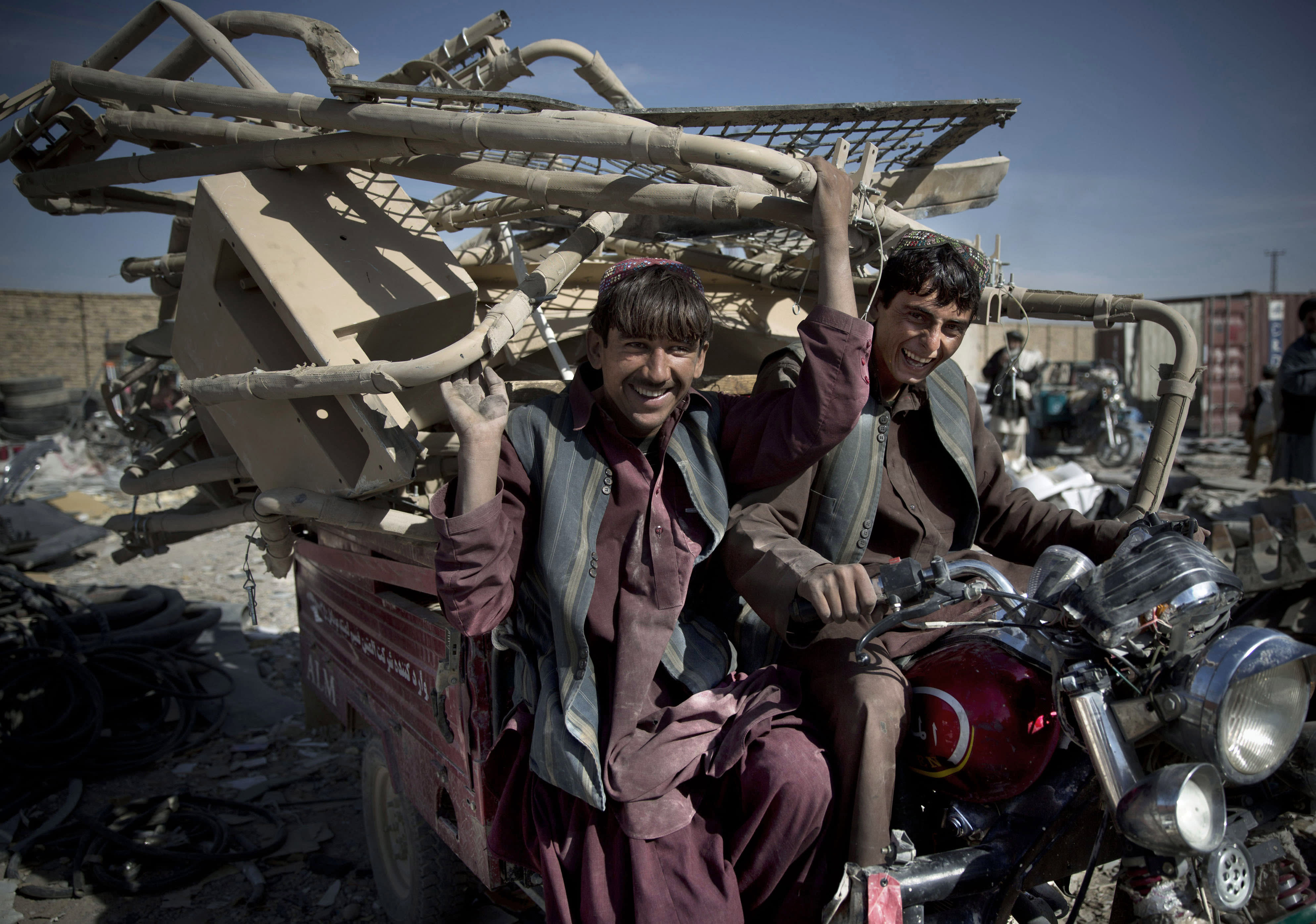 This Saturday, Nov. 2, 2013 photo shows Afghan scrap collectors transport a load of destroyed U.S. equipment from the departing military in Kandahar, southern Afghanistan. As the final withdrawal of U.S. and NATO troops approaches at the end of 2014, the U.S. military is getting rid of equipment that is either too expensive to ship back to the United States or if it is sold as working equipment could be used by insurgents. (AP Photo/Anja Niedringhaus)