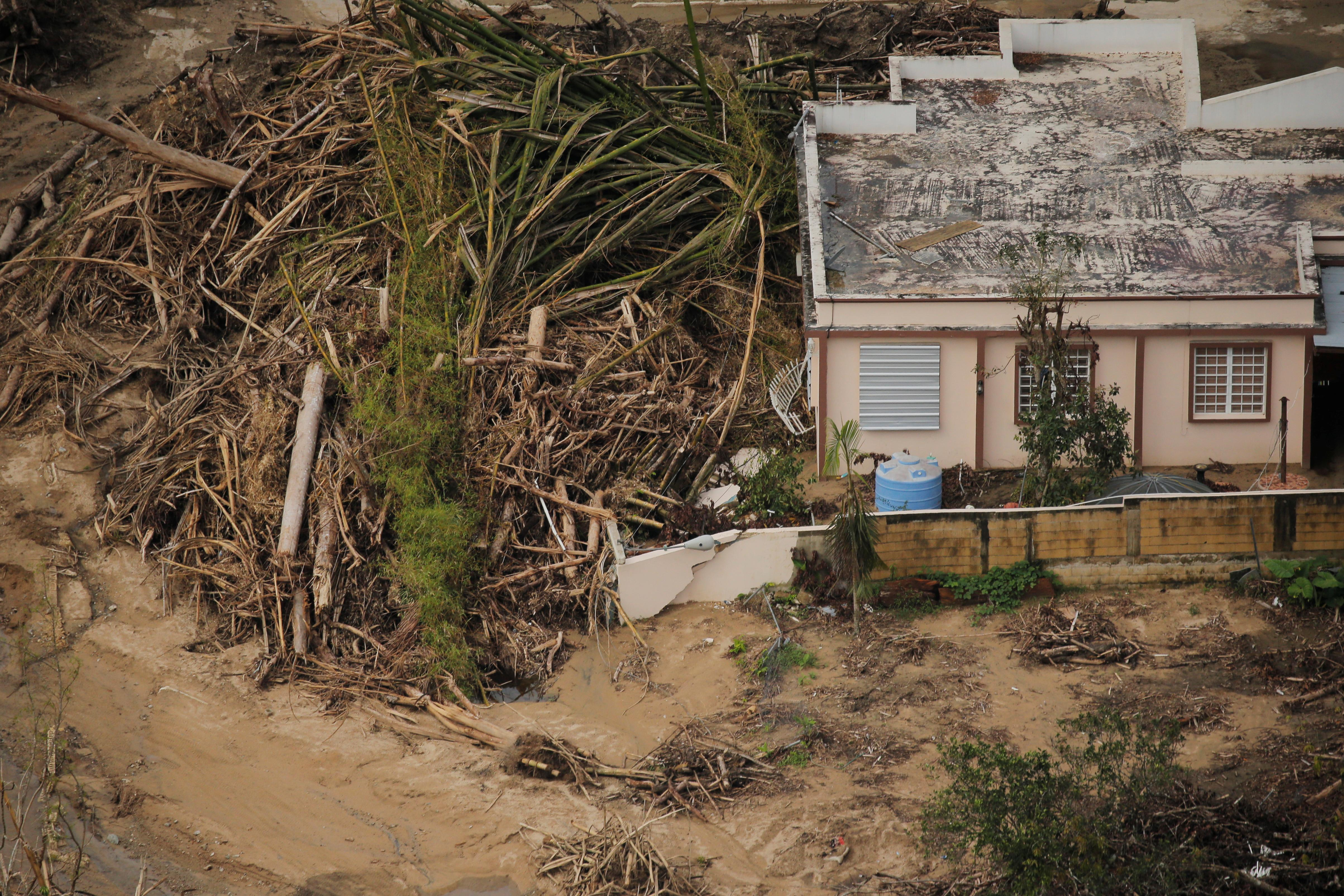 <p>Debris left by a flooded river is piled against a home, seen from the air, during recovery efforts following Hurricane Maria near Utuado, Puerto Rico, Oct.10, 2017. (Photo: Lucas Jackson/Reuters) </p>