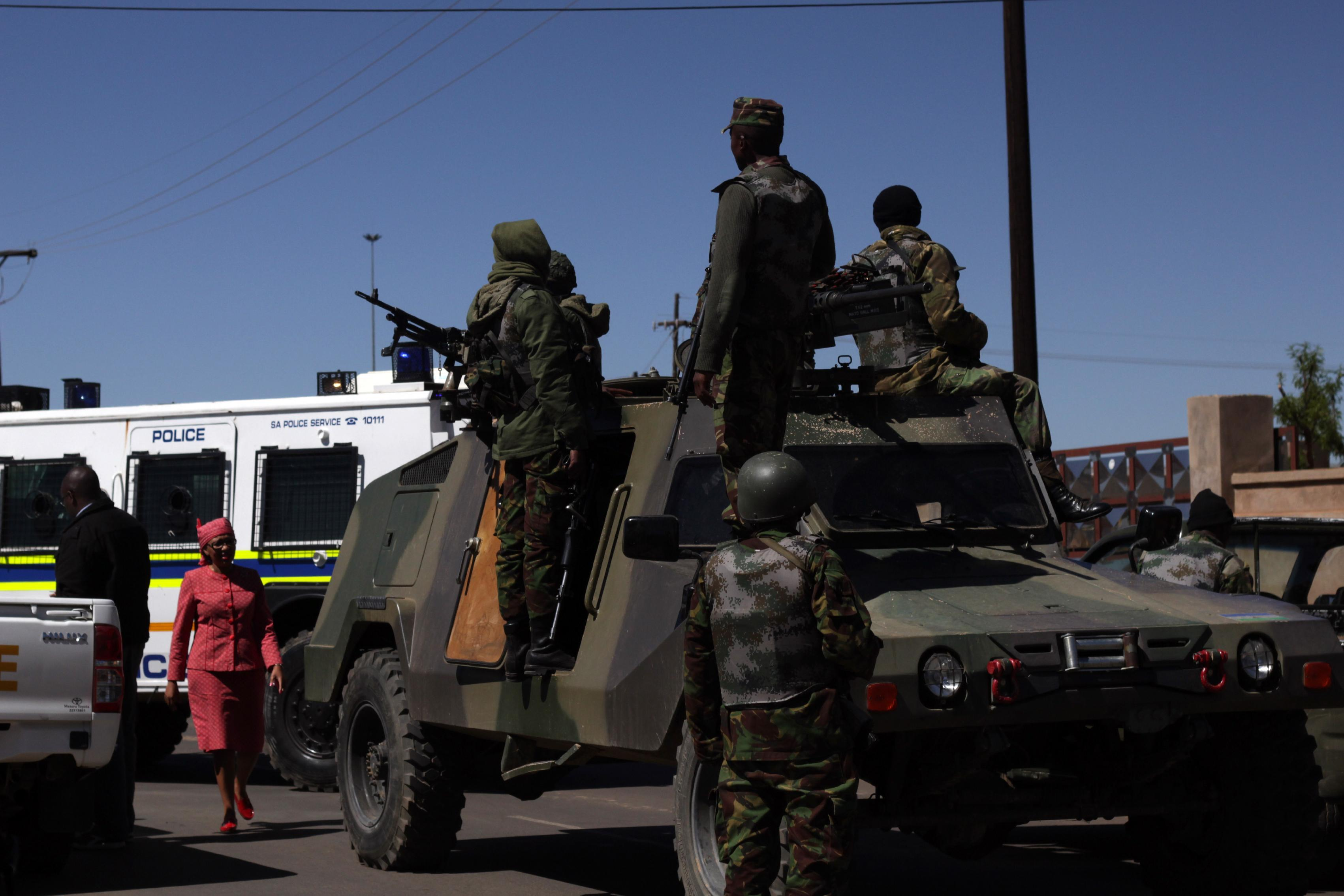 Members of the Lesotho national are seen next to a South African Police armoured vehicle outside Maseru on October 1, 2014 (AFP Photo/Hlompho Letsielo)