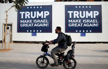 A man cycles past signs bearing the name of U.S. President-elect Republican Donald Trump in Tel Aviv, Israel November 14, 2016. REUTERS/Baz Ratner