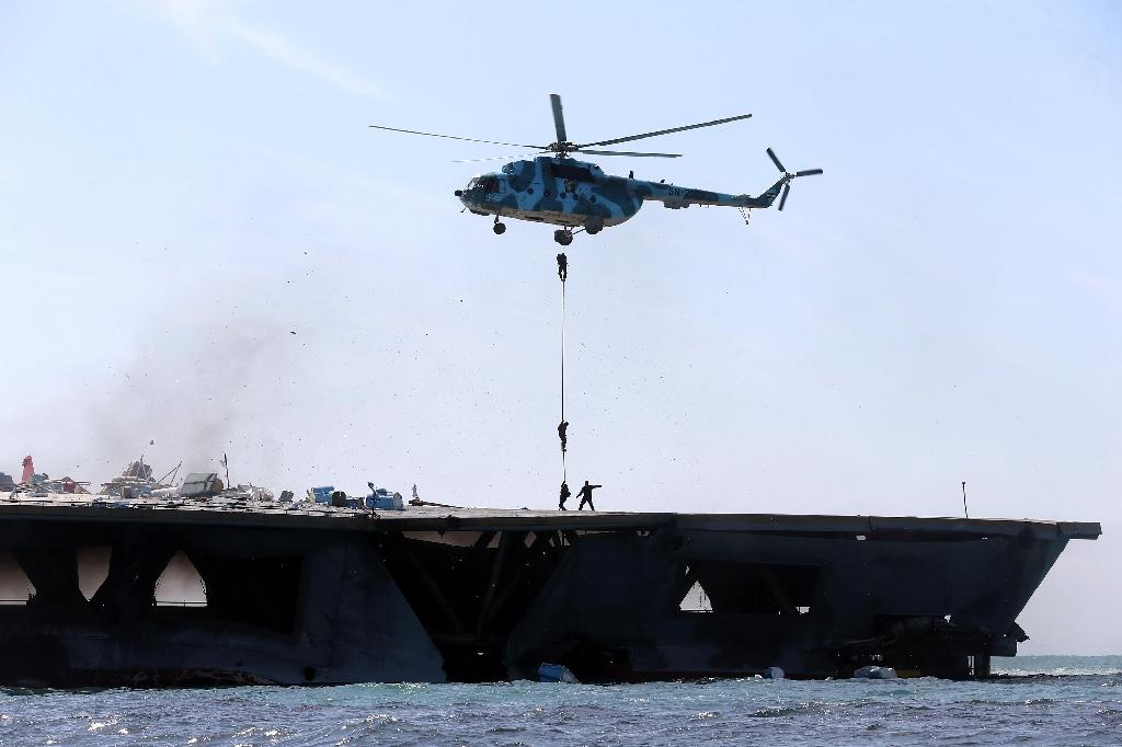 Iran's elite Revolutionary Guard troops rappel down a helicopter on a naval vessel during a military drill in the Strait of Hormuz in southern Iran on February 25, 2015 (AFP Photo/Hamed Jafarnejad)