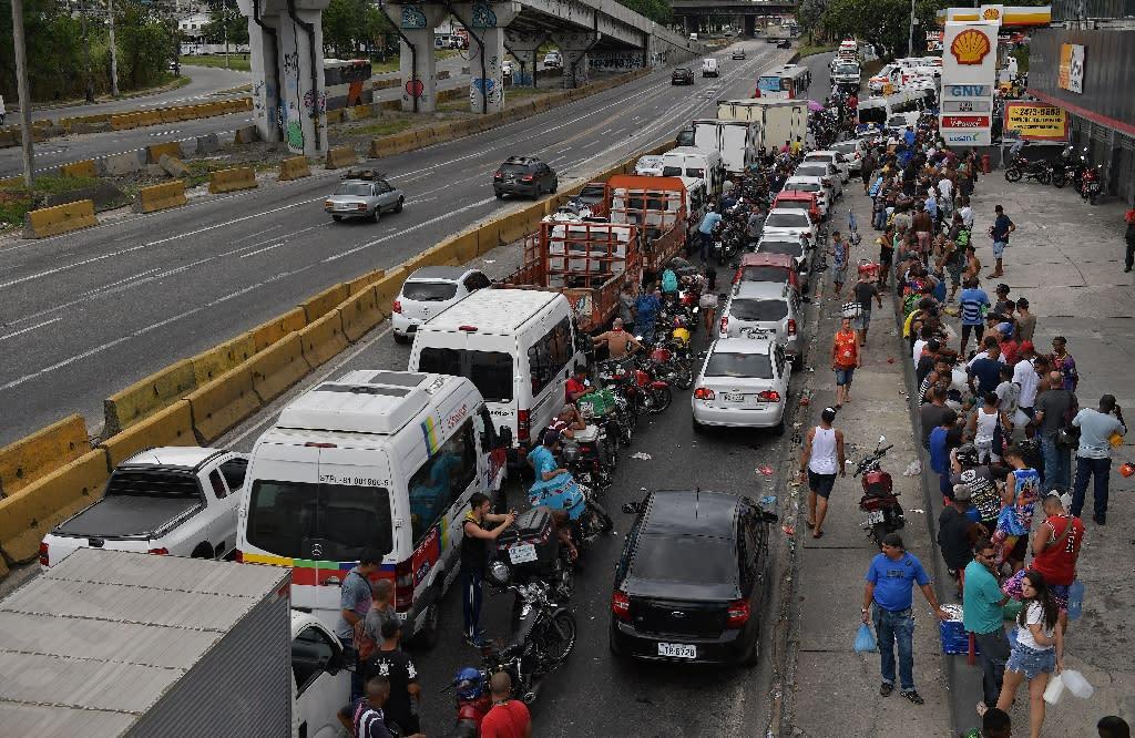People queue for fuel at a petrol station in Rio de Janeiro (AFP Photo/Carl DE SOUZA)