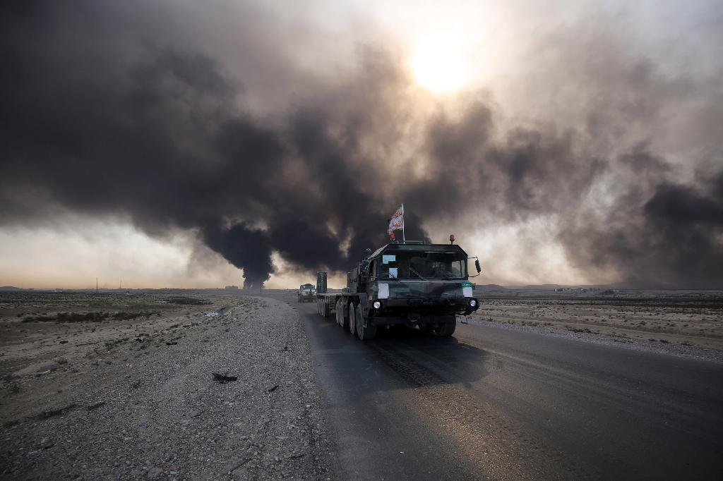 Iraqi army vehicle drives down a road east of Mosul, northern Iraq, on October 22, 2016, as displaced families flee areas of unrest during an operation to retake the city from Islamic State (IS) group jihadists (AFP Photo/Ahmad Al-Rubaye)