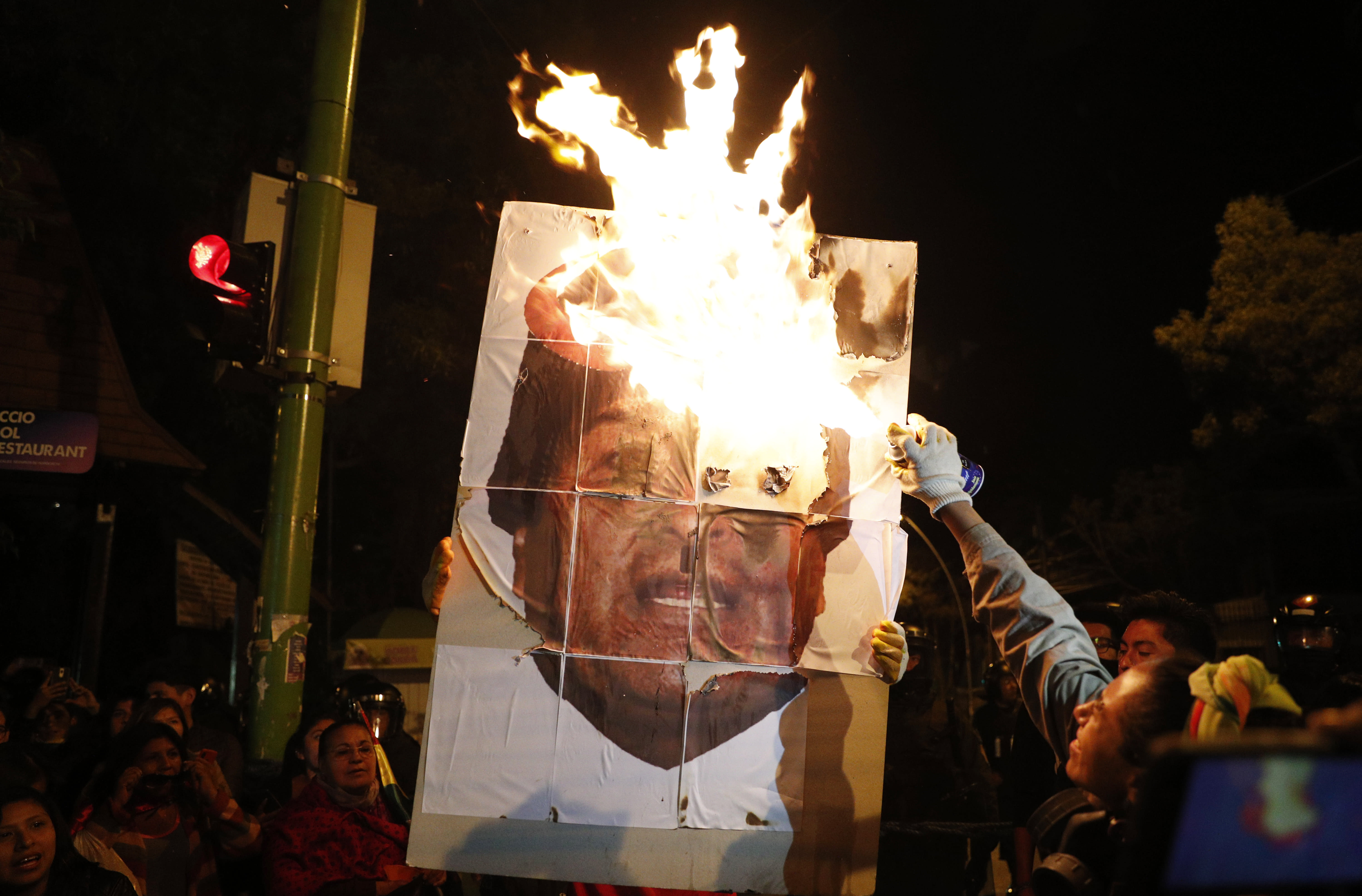 Anti-government protesters burn a picture President Evo Morales during a march demanding a second round presidential election, in La Paz, Bolivia, Saturday, Oct. 26, 2019. Bolivia's official vote tally was revealed Friday pointing to an outright win for incumbent Evo Morales in a disputed presidential election that has triggered protests and growing international pressure on the Andean nation to hold a runoff ballot. (AP Photo/Juan Karita)
