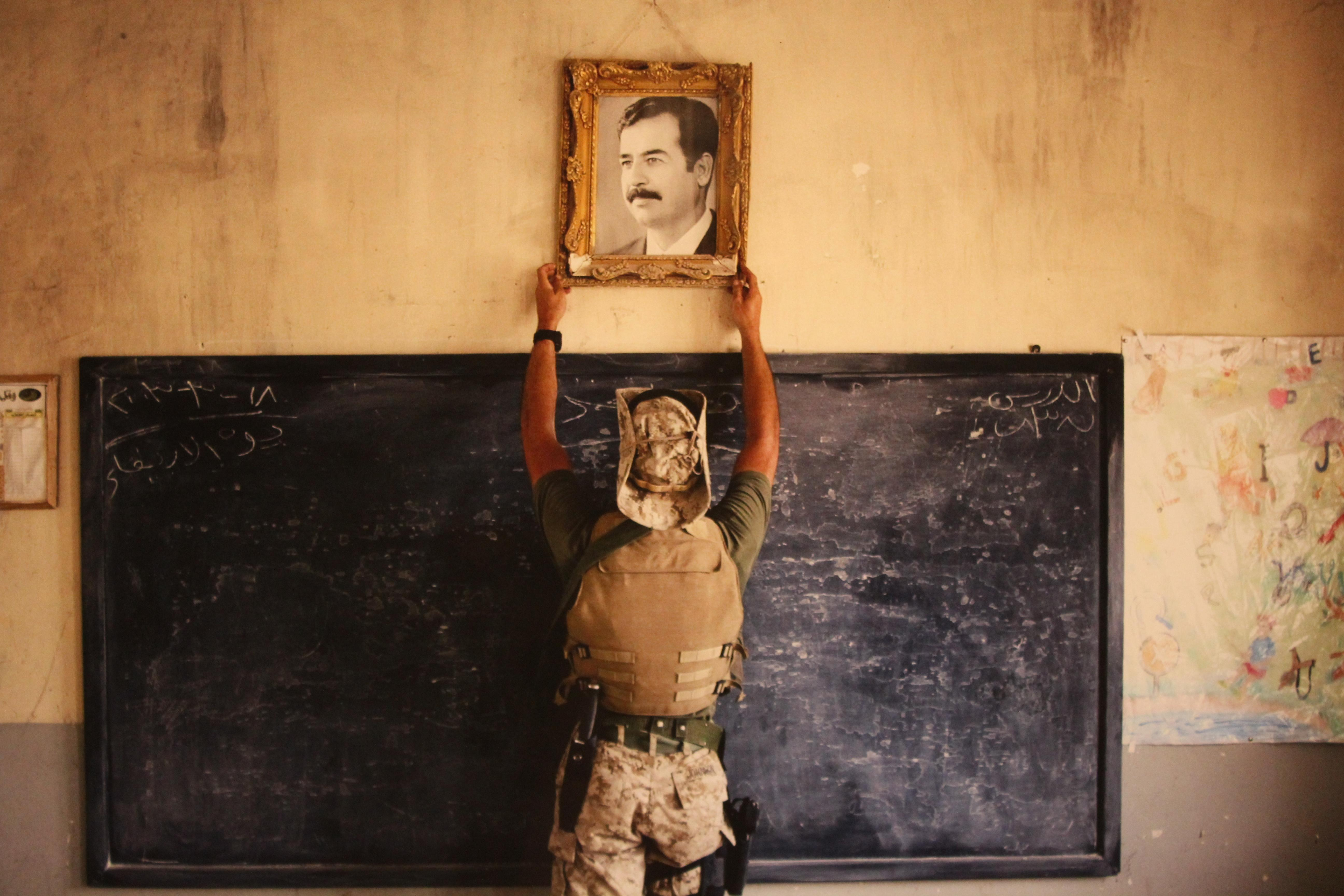 <p>A U.S. Marine pulls down a picture of Saddam Hussein at a school April 16, 2003 in Al-Kut, Iraq. A combination team of Marines, Army and Special Forces went to schools and other facilities in Al-Kut looking for weapons caches and unexploded bombs in preparation for removing and neutralizing them. </p>