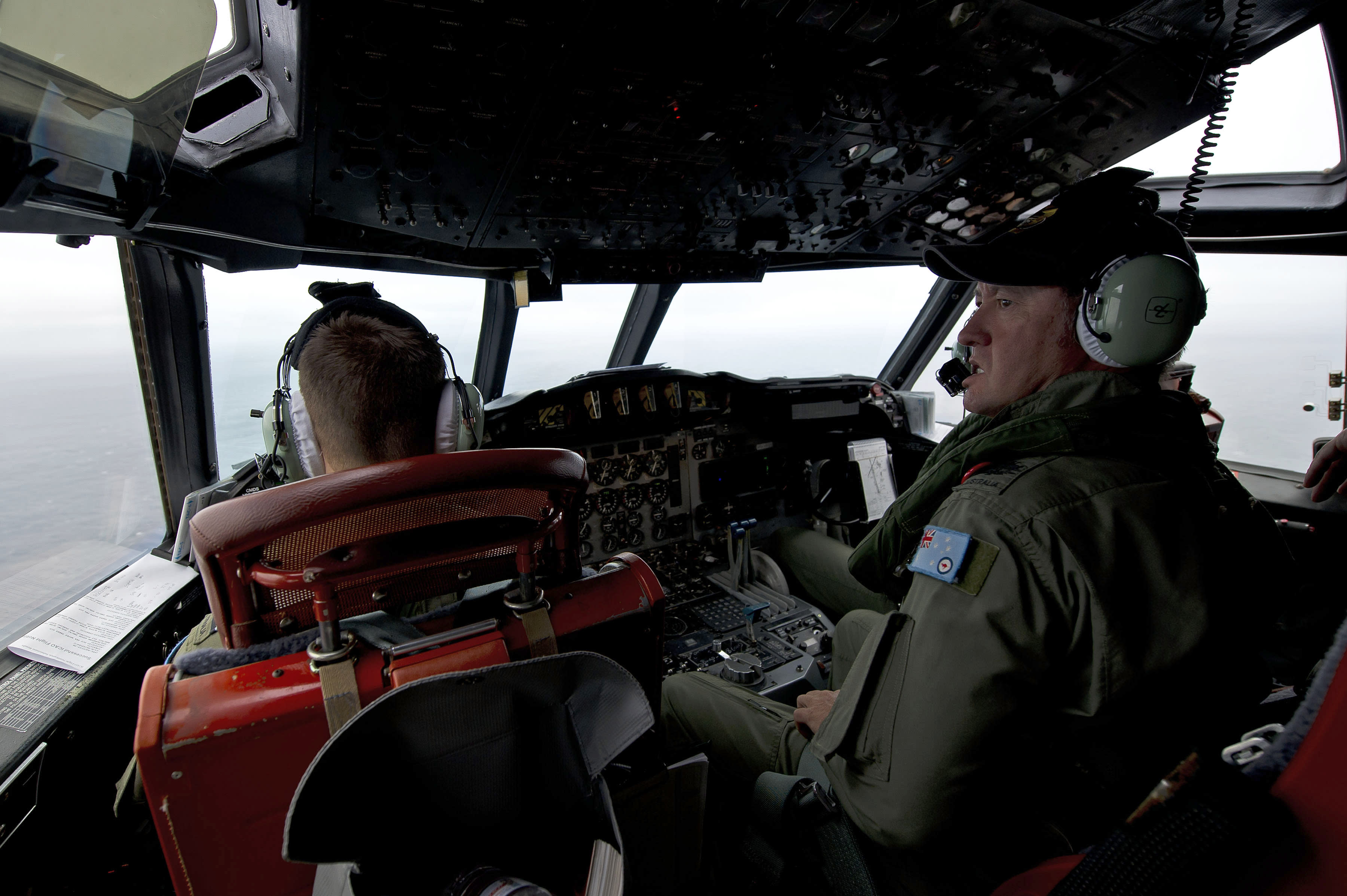 This Wednesday, March 19, 2014 photo released by the Australia Defence Department, shows Royal Australian Air Force Flight Engineer, Warrant Officer Ron Day from 10 Squadron, on board an AP-3C Orion over the Southern Indian Ocean off the Western Australian coast during a search operation for the missing Malaysian Airlines flight MH370. Australian Prime Minister Tony Abbott said Thursday that two objects possibly related to the missing flight have been spotted on satellite imagery in the Indian Ocean and an air force aircraft was diverted to the area to try to locate them. (AP Photo/Australia Defence Department, Hamish Paterson)