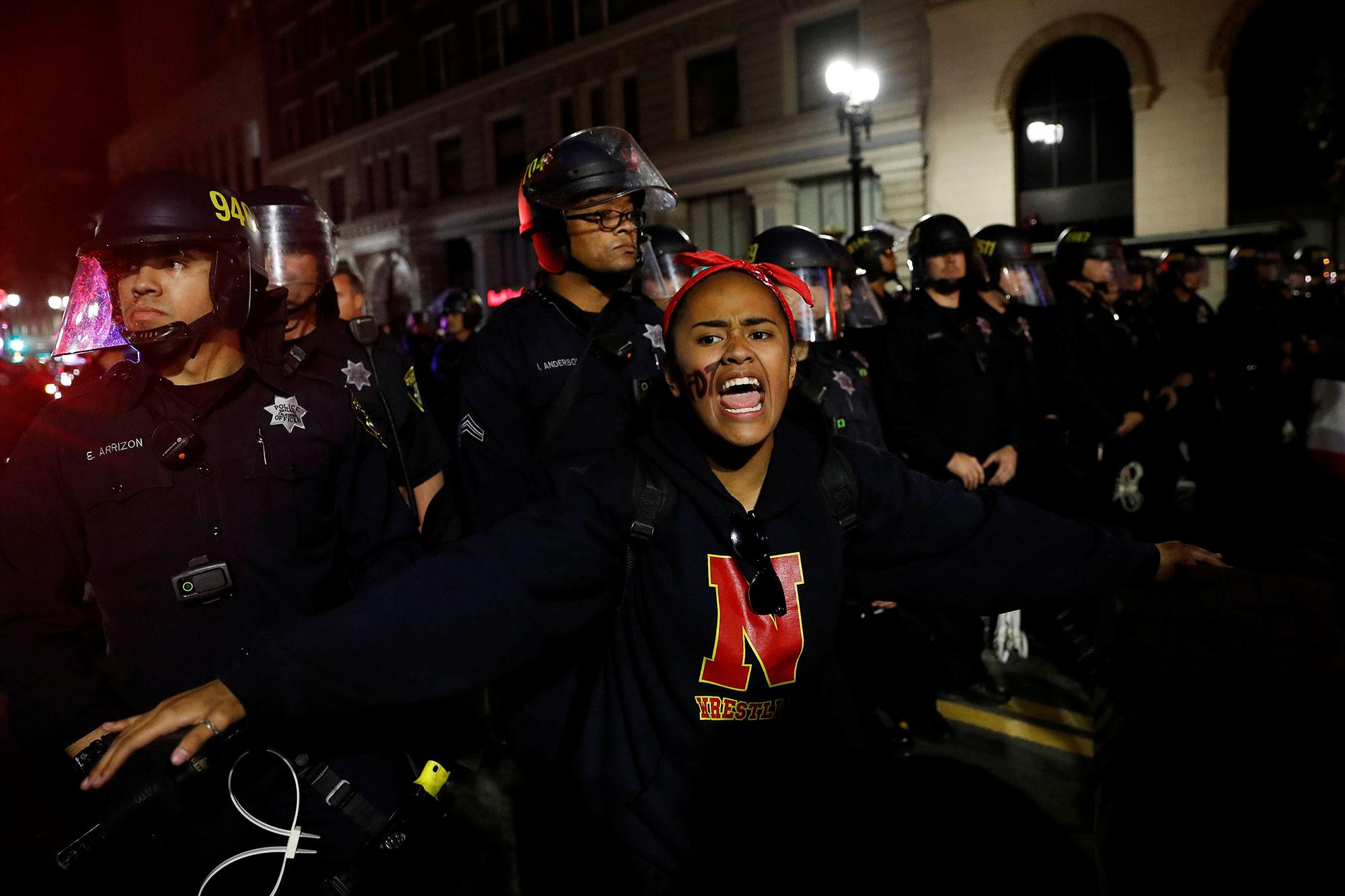 <p>A demonstrator pleads others to stand back from the police line during a demonstration following the election of Donald Trump as President of the United States, in Oakland, Calif., on Nov. 10, 2016. (Photo: Stephen Lam/Reuters) </p>