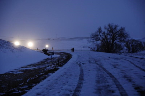 A couple stands lit by police lights near Backwater Bridge just outside of the Oceti Sakowin camp during ongoing demonstrations against the Dakota Access pipeline near the Standing Rock Indian Reservation, near Cannon Ball, North Dakota