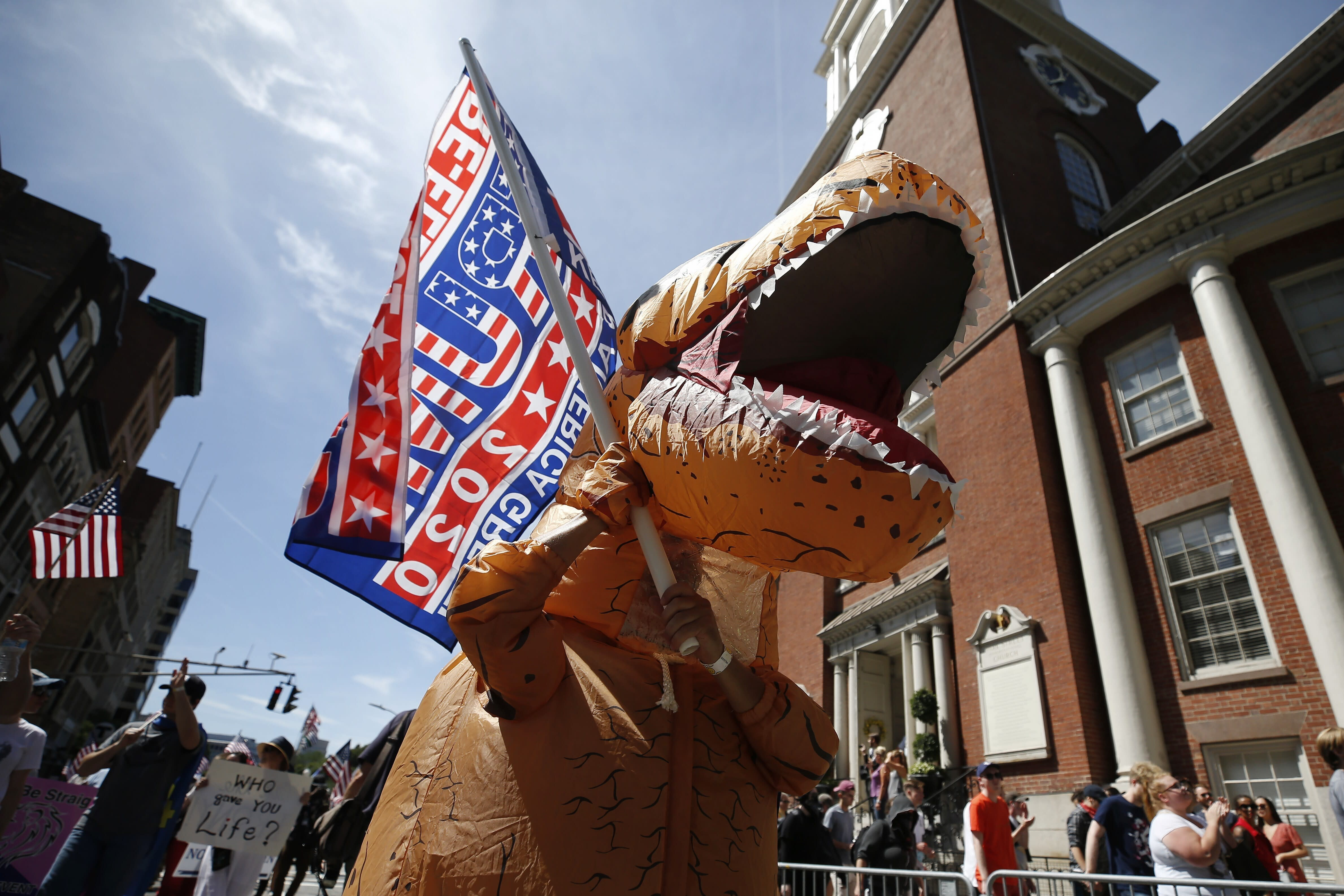 """A marcher wears a dinosaur costume during the Straight Pride Parade in Boston, Saturday, Aug. 31, 2019. Several dozen marchers and about as many counter-demonstrators have gathered in Boston for a """"straight pride"""" parade. The organizers say they believe straight people are an oppressed majority. (AP Photo/Michael Dwyer)"""