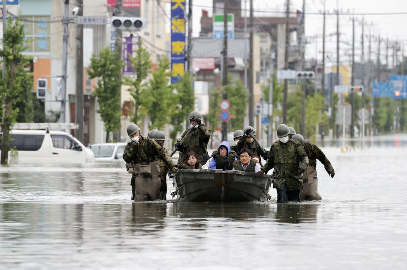 Local residents are rescued by Japan Self-Defense Force soldiers using by a boat on a flooded road caused by heavy rain in Omuta, Japan
