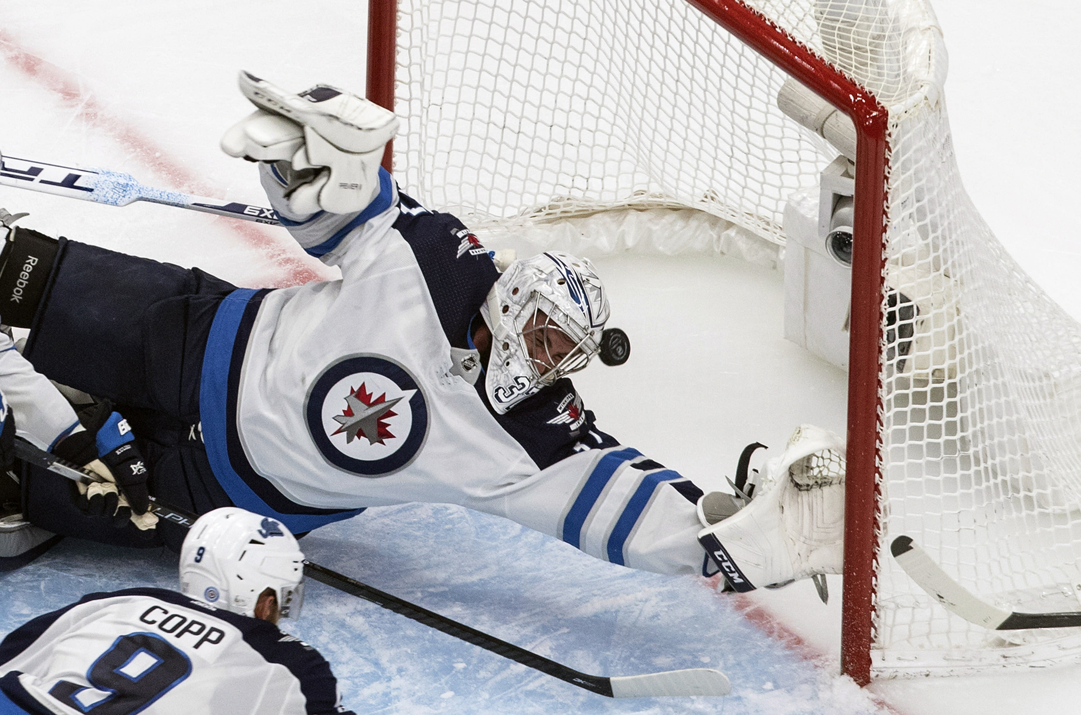 Winnipeg Jets goalie Connor Hellebuyck (37) is scored on by Calgary Flames' Johnny Gaudreau as Jets' Andrew Copp defends during the second period of an NHL hockey playoff game Saturday, Aug. 1, 2020 in Edmonton, Alberta. (Jason Franson/The Canadian Press via AP)