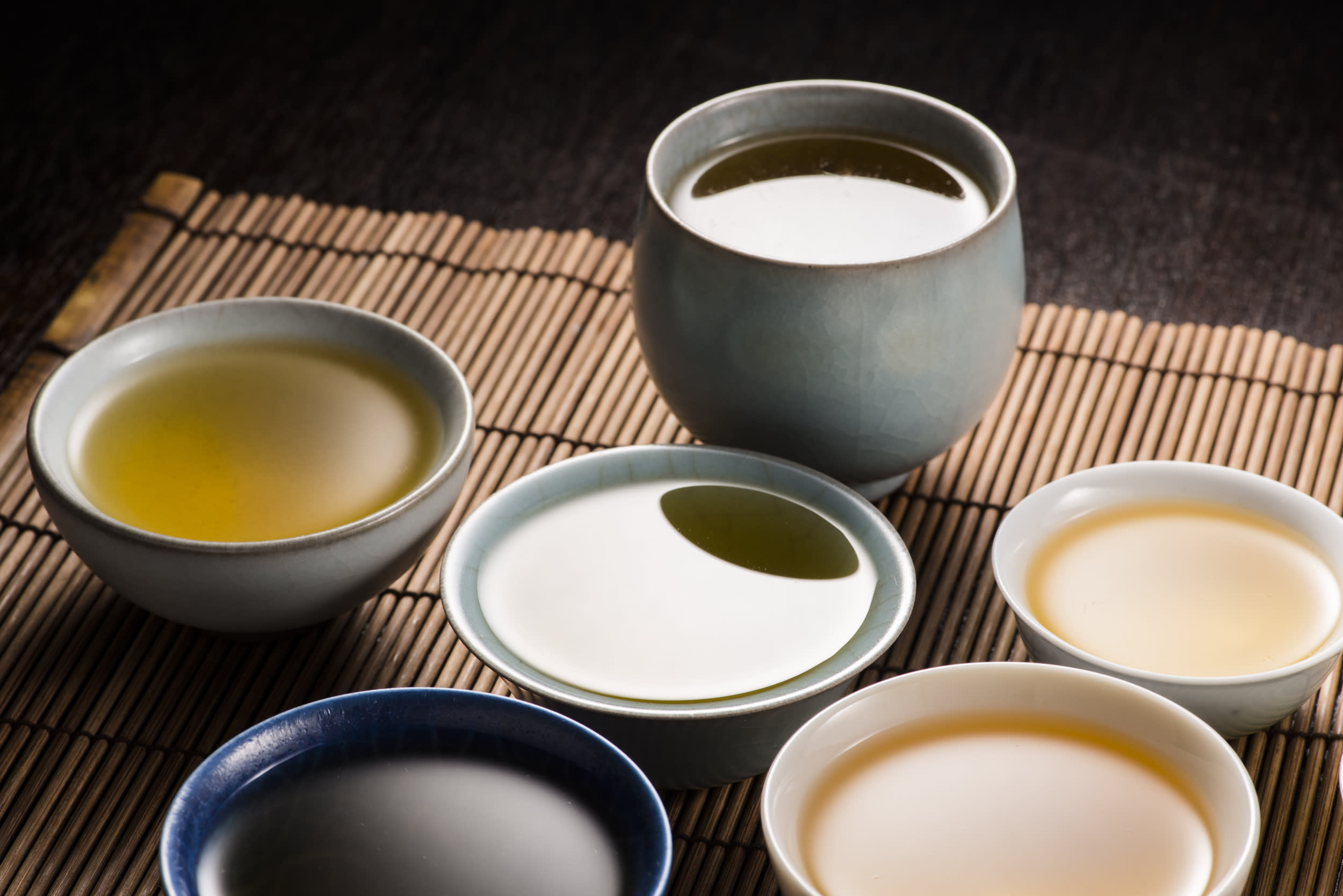 Chinese tea Ceremony, it is about Chinese culture. Chinese oolong tea on a bamboo tray. There are tea cup and teapot. The drink is hot. And the color are yellow,brown,green and blue. And there is highlight reflection on the water surface.