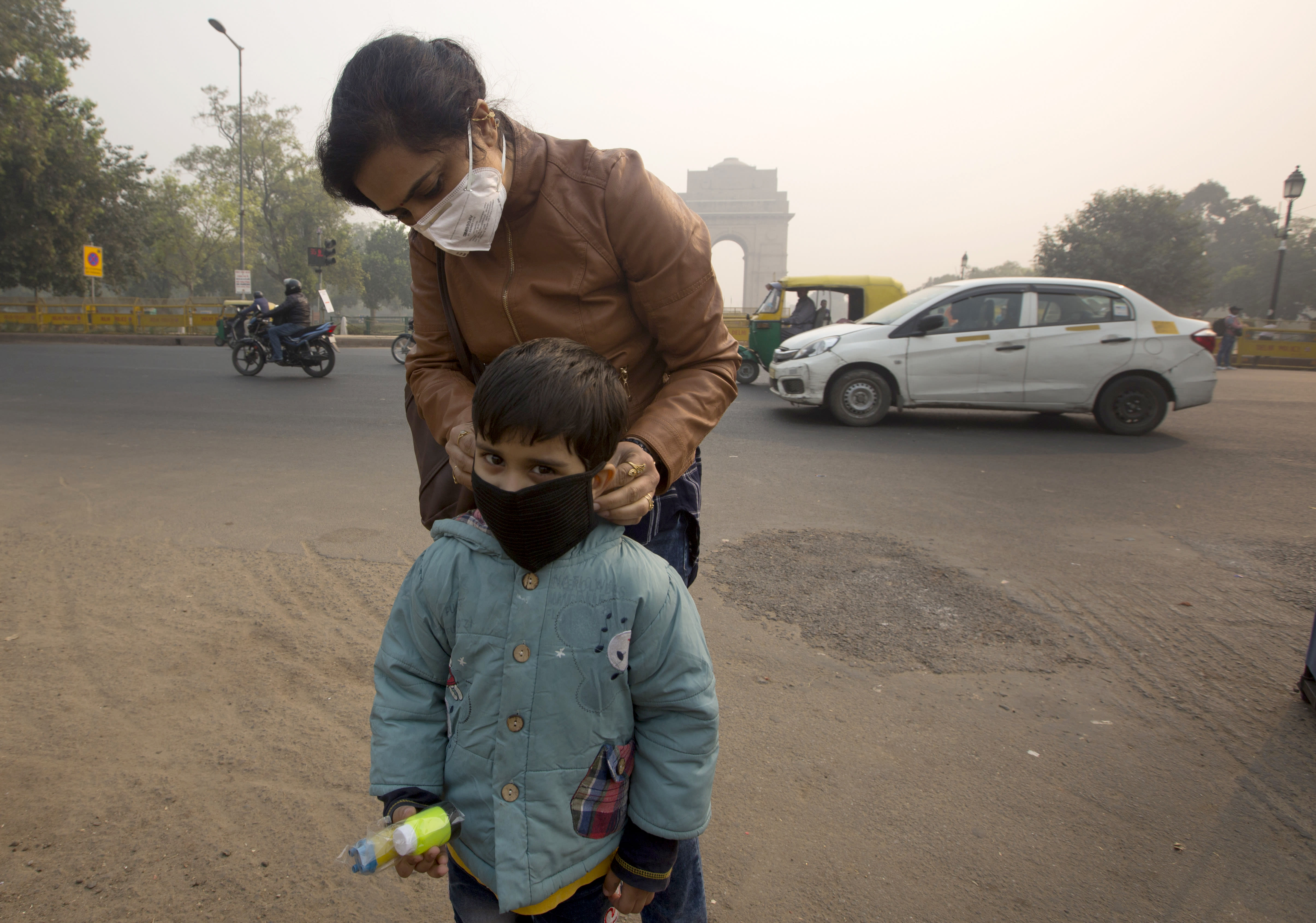 An Indian mother puts a mask to her son a day after Diwali festival in New Delhi, India, Thursday, Nov. 8, 2018. Toxic smog shrouds the Indian capital as air quality falls to hazardous levels with tens of thousands of people setting off massive firecrackers to celebrate the major Hindu festival of Diwali on Wednesday night. (AP Photo/Manish Swarup)